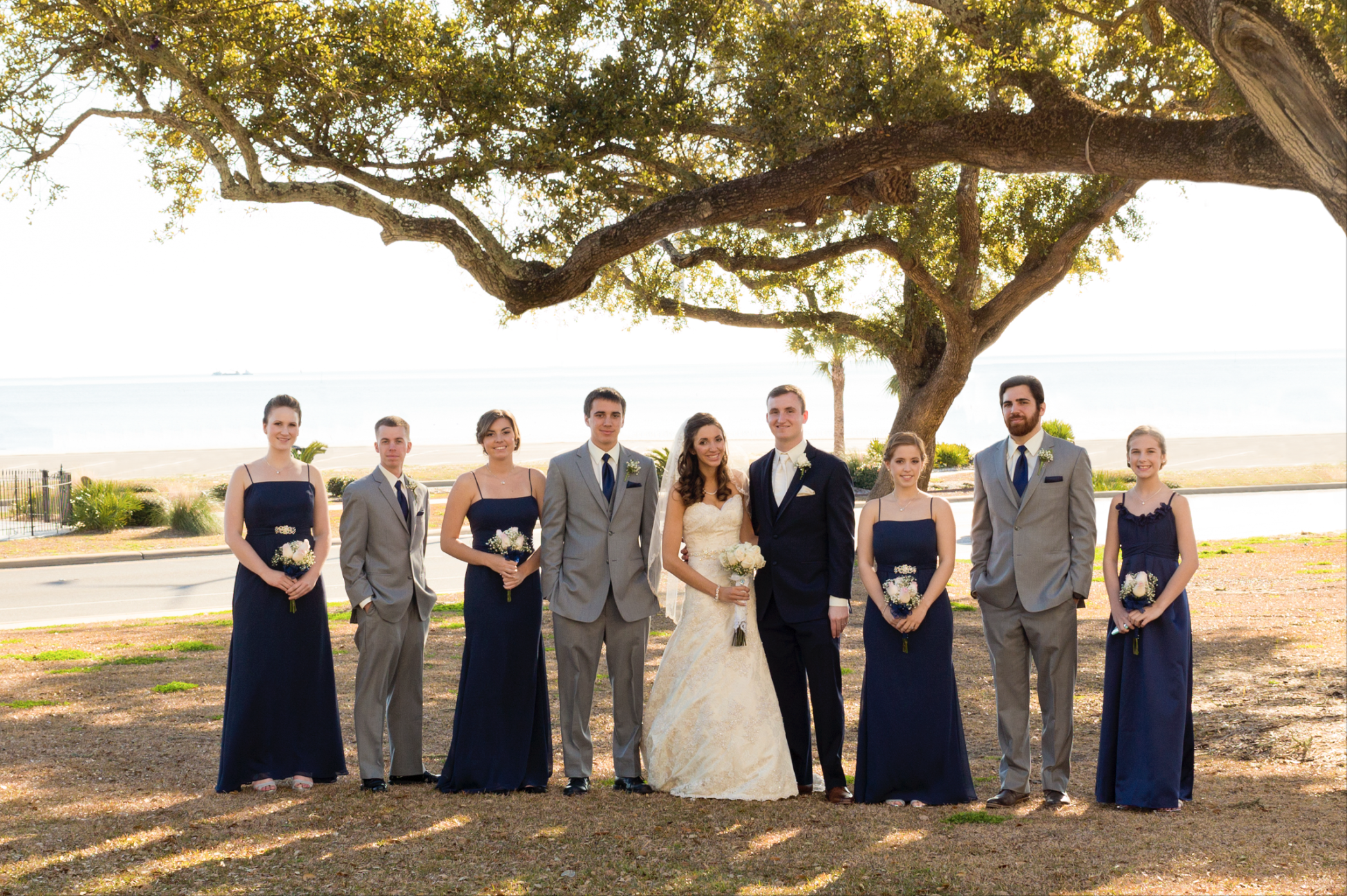 outdoor wedding party group photo with live oak tree