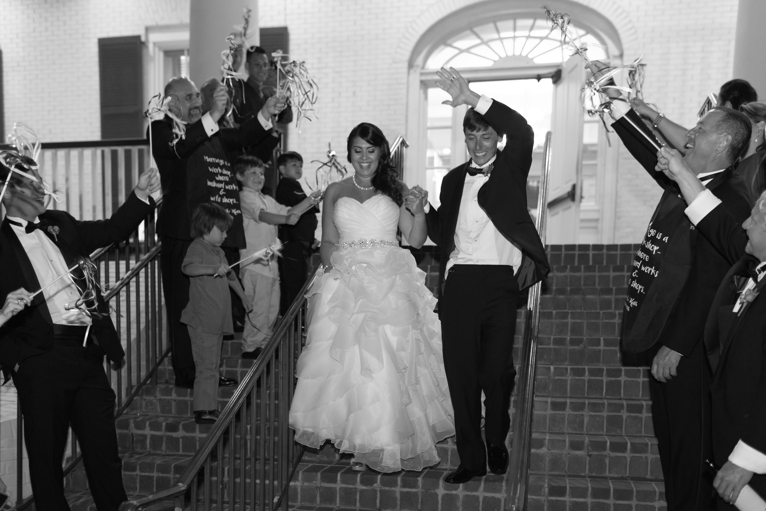bride and groom leaving reception with wedding wands