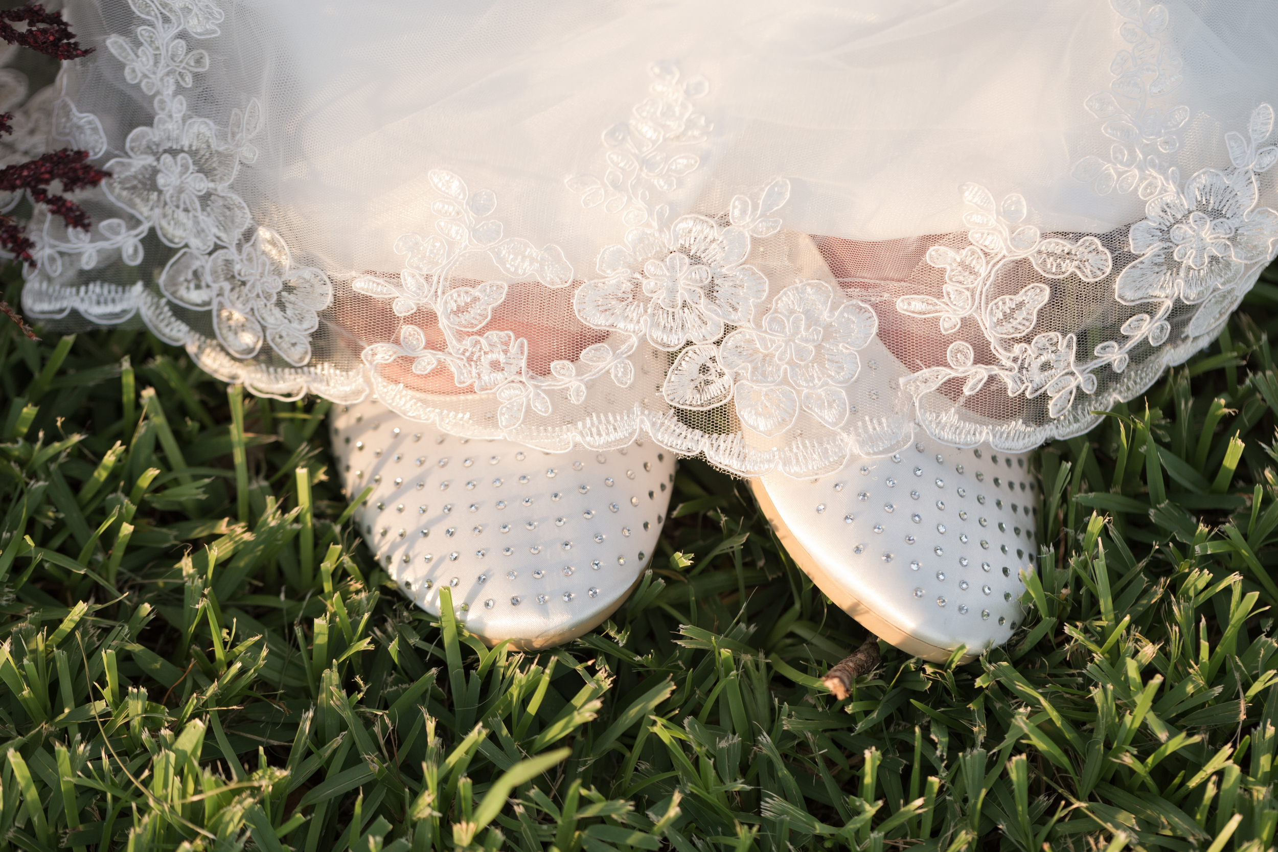 flat bridal shoes with rhinestones and lace veil in grass