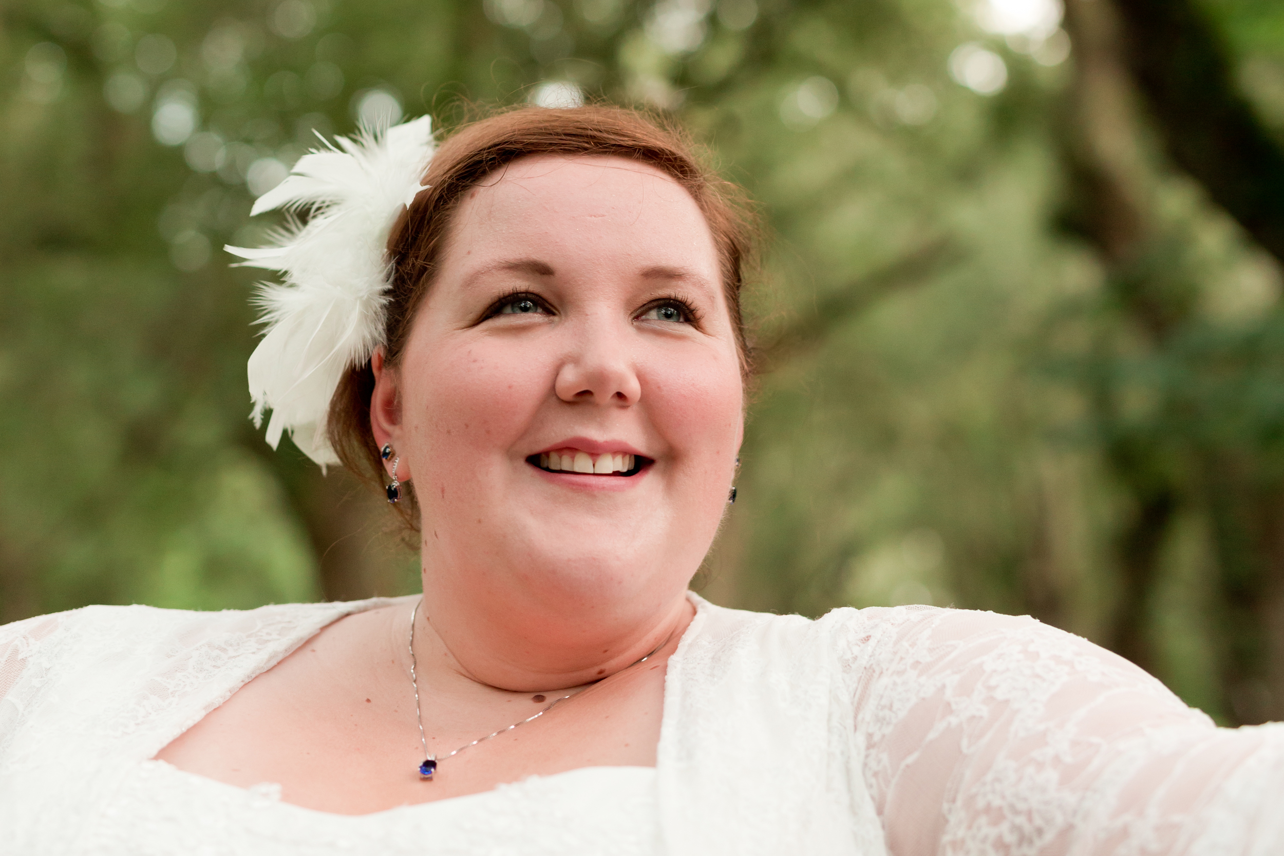 relaxed, happy, candid bride with feather fascinator