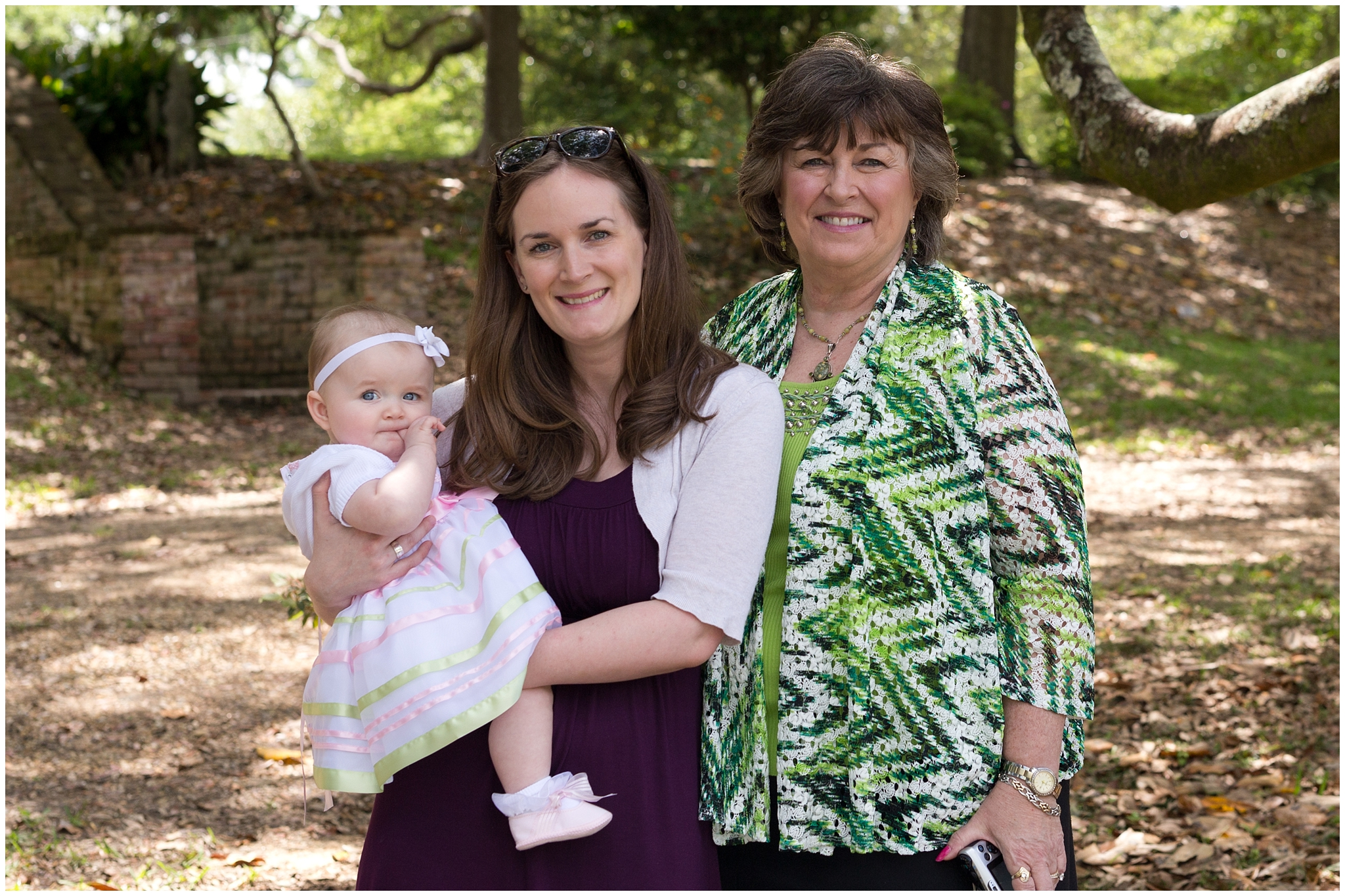 baby girl in Sunday dress with mother and grandmother