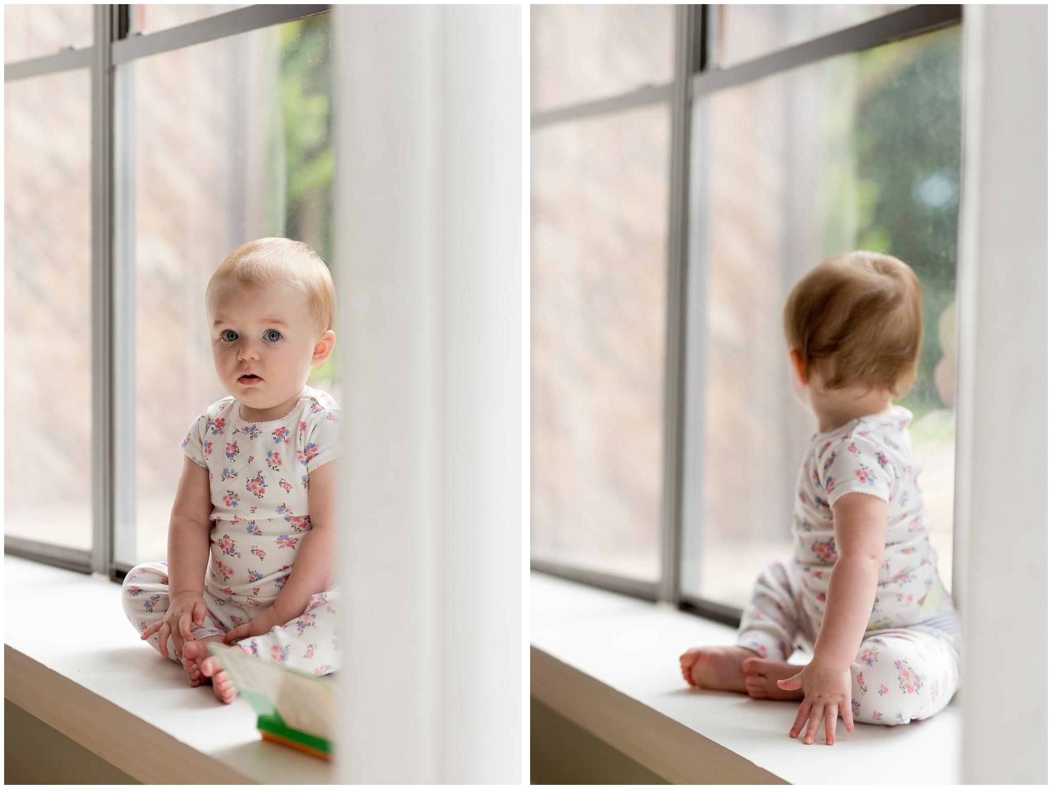 adorable baby girl sitting in windowsill in pajamas