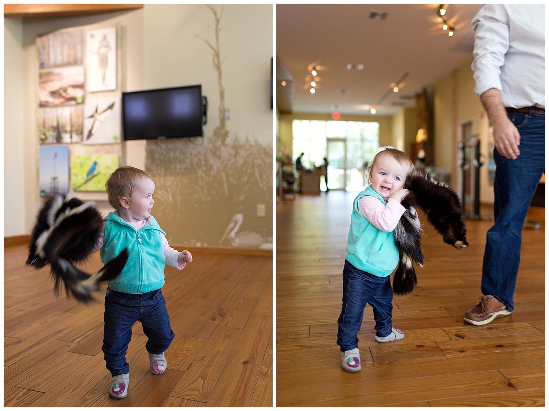 girl playing with skunk skin at Pascagoula River Audubon Center