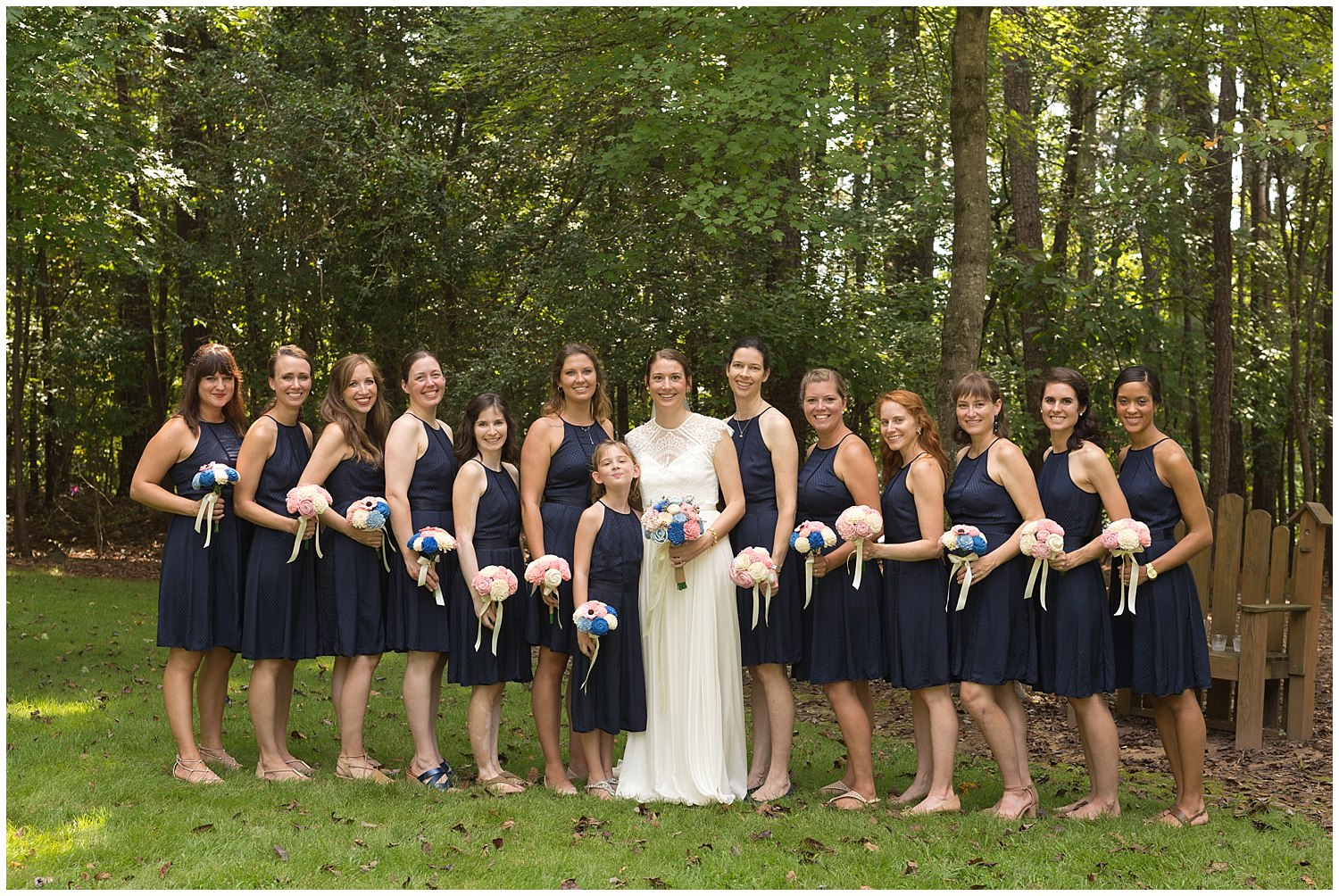 bridesmaids with navy blue dresses and pink bouquets