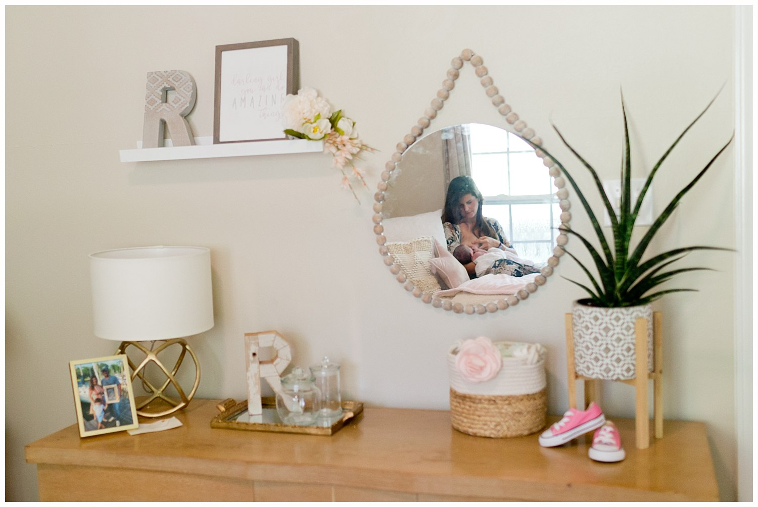 mother nursing baby girl in nursery - mirror reflection with cute decor