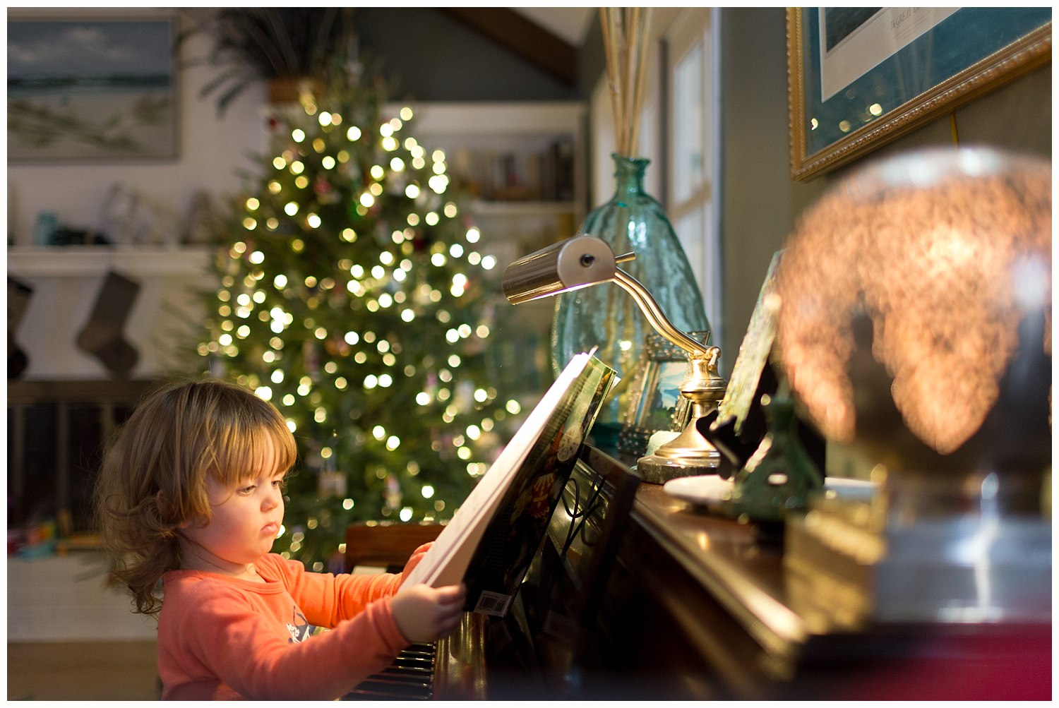 toddler girl playing piano with Christmas tree in the background