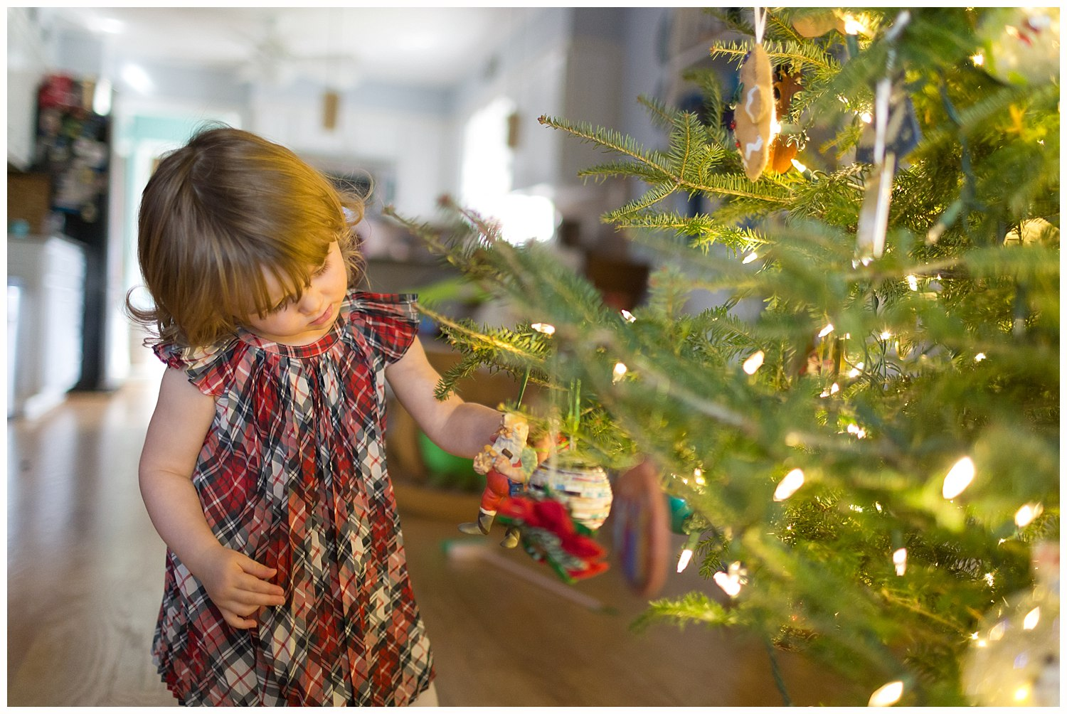 little girl decorating Christmas tree - Ocean Springs lifestyle photographer