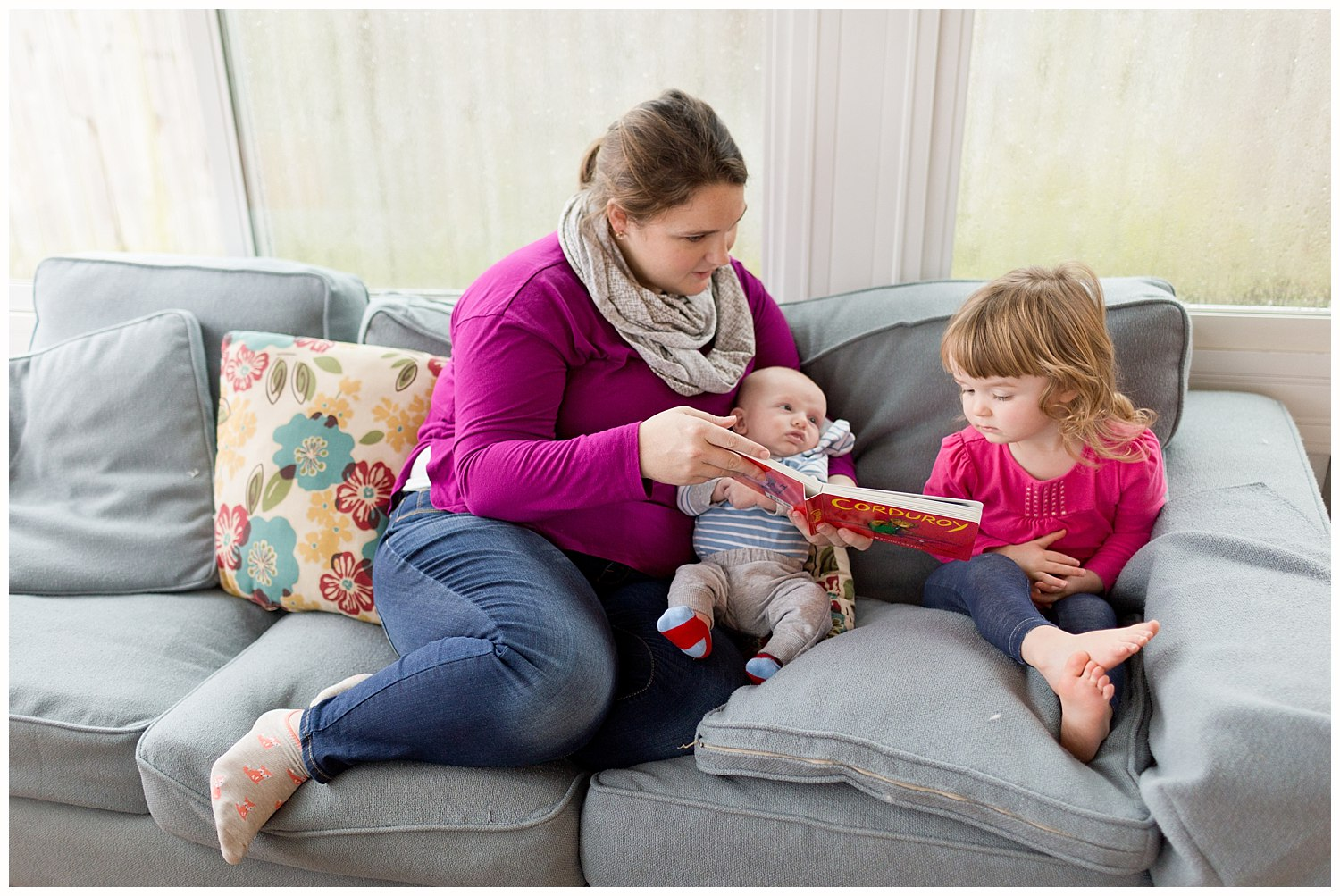 mom reading Corduroy book to baby boy and toddler girl