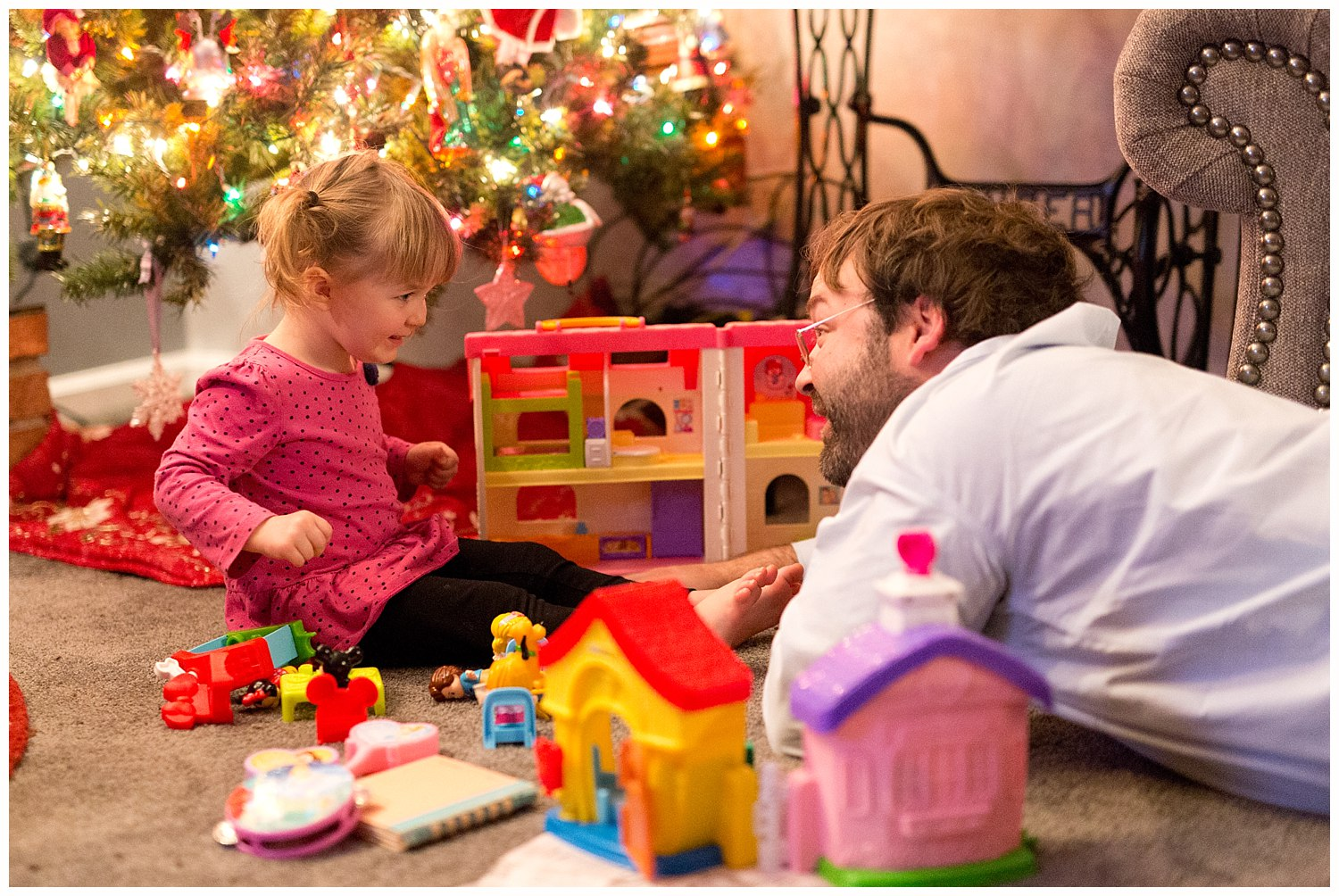 daddy and daughter playing under Christmas tree