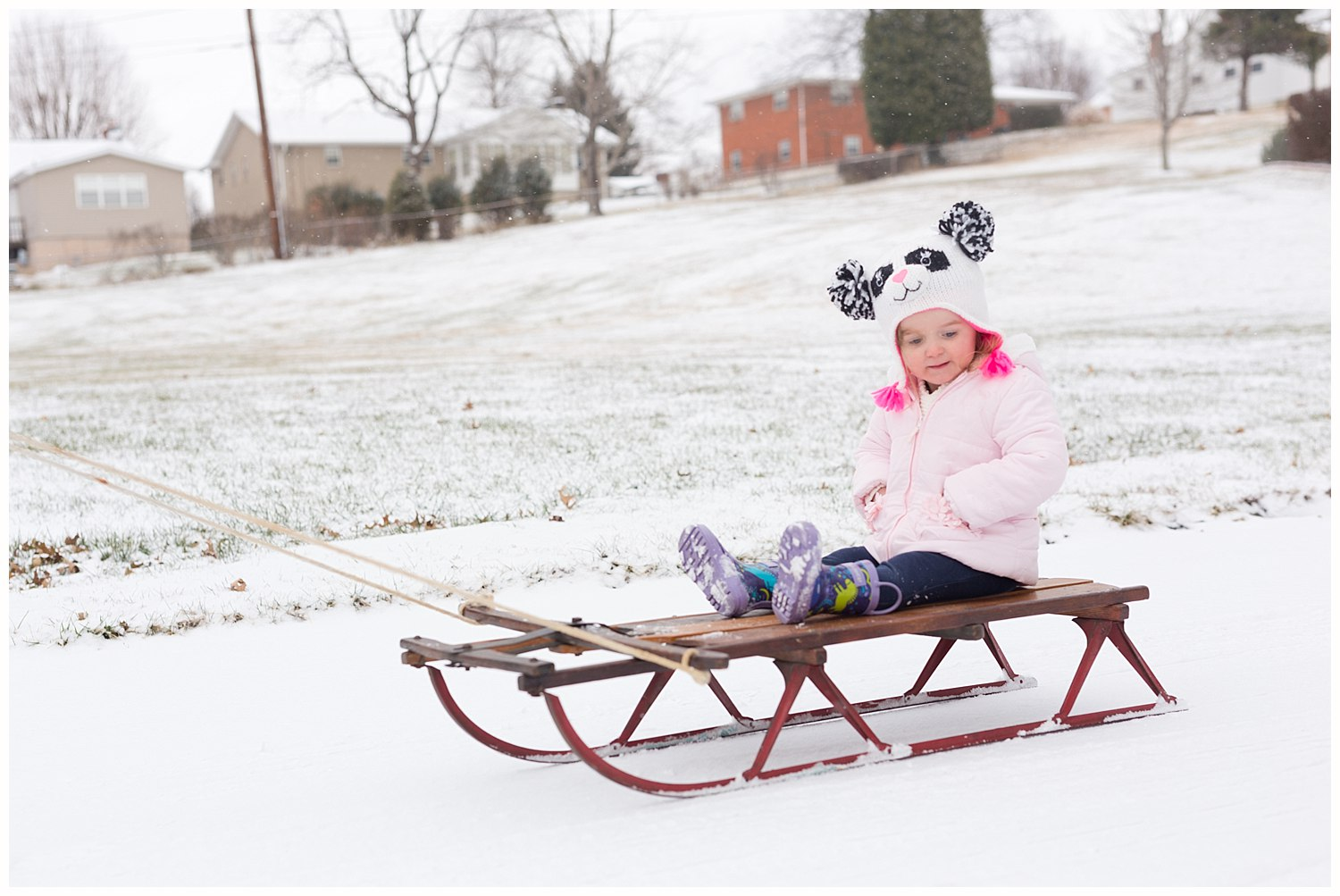 two-year-old girl on antique sled in the snow