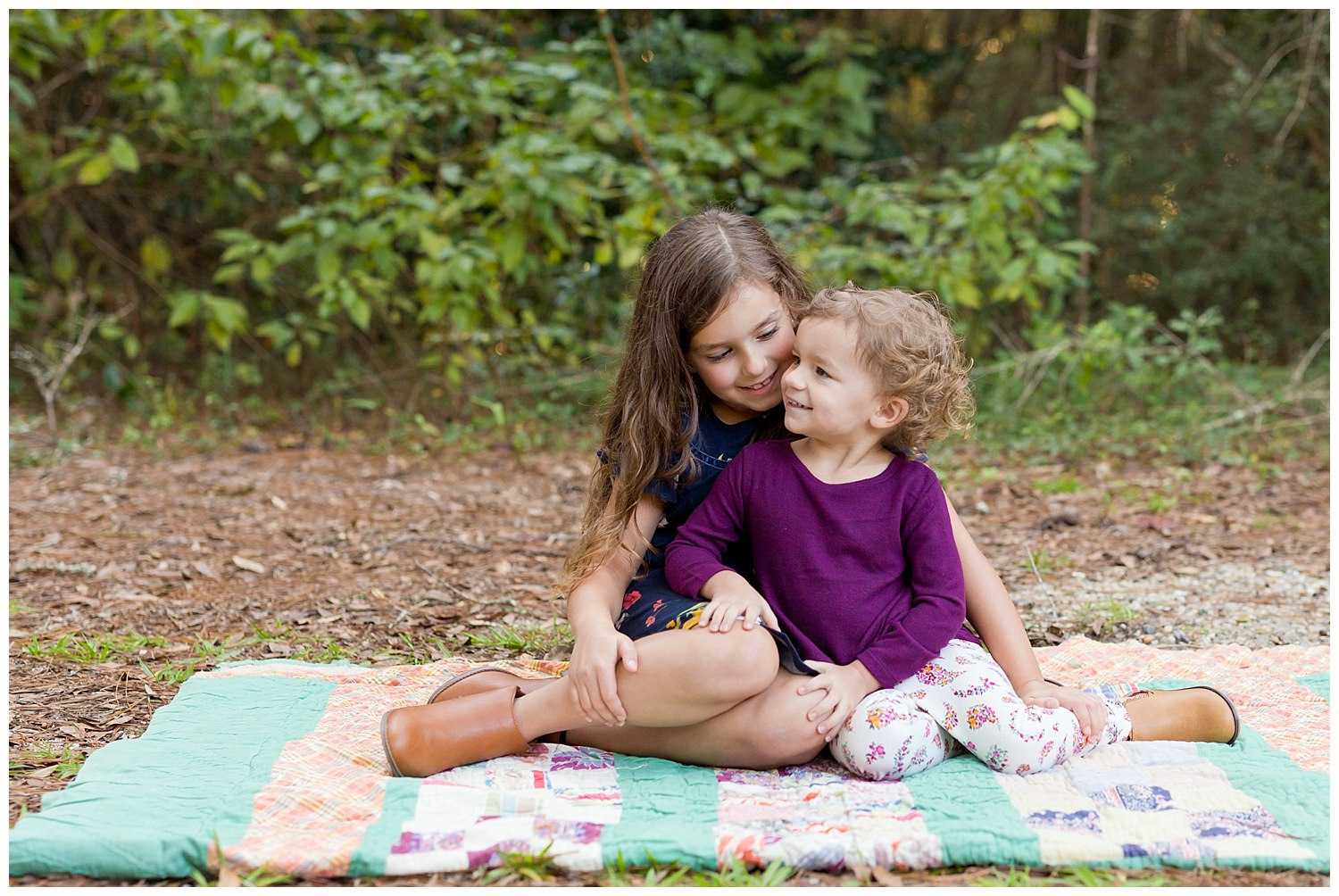 photo of two sisters on quilt in the woods