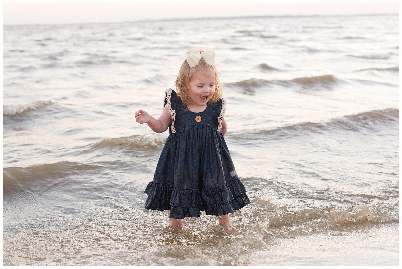 little girl splashing in ocean water
