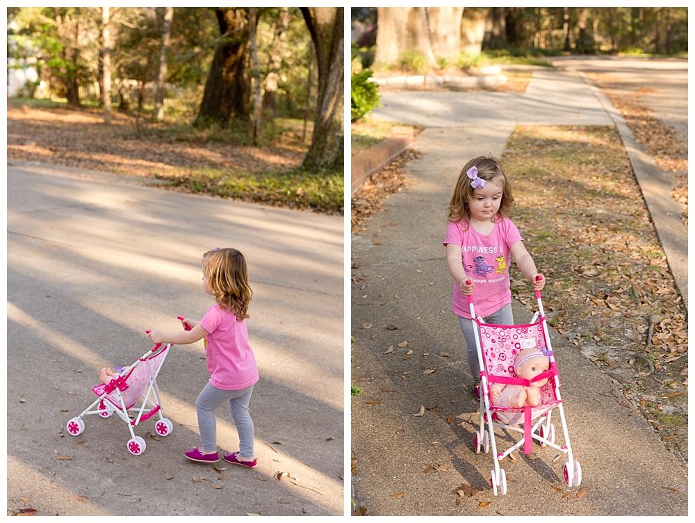 toddler girl walking baby doll in stroller
