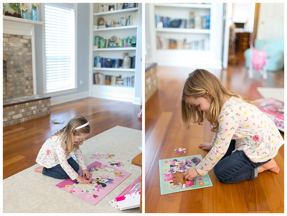 little girl doing Minnie Mouse puzzles in living room