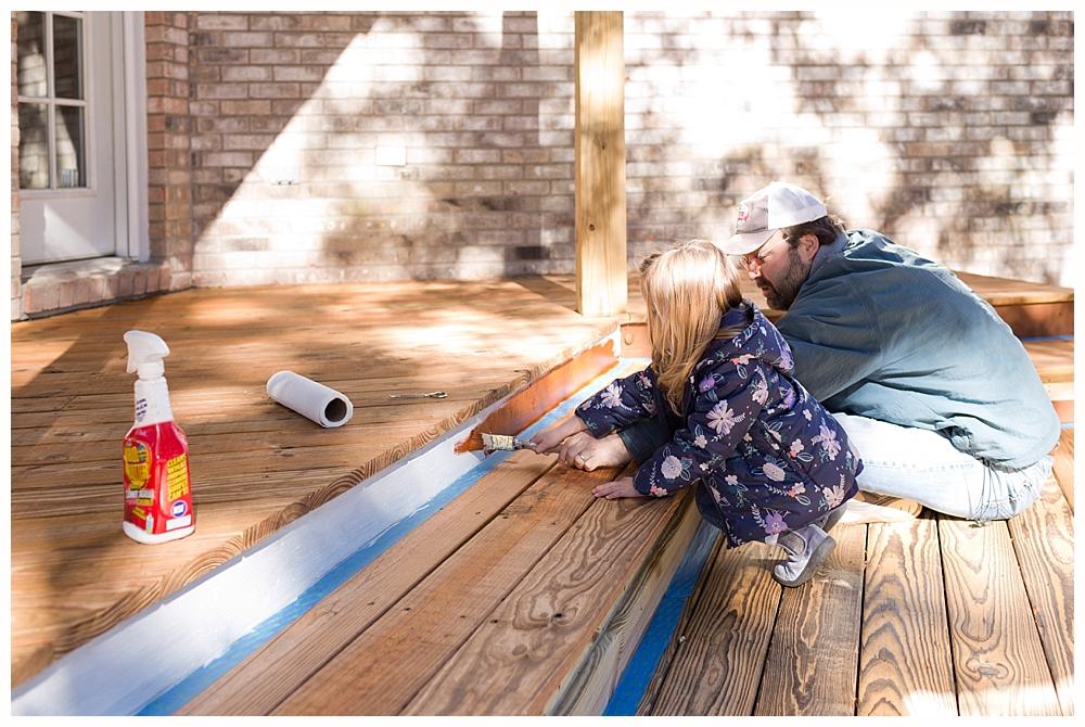 little girl helping dad paint deck in Ocean Springs, MS