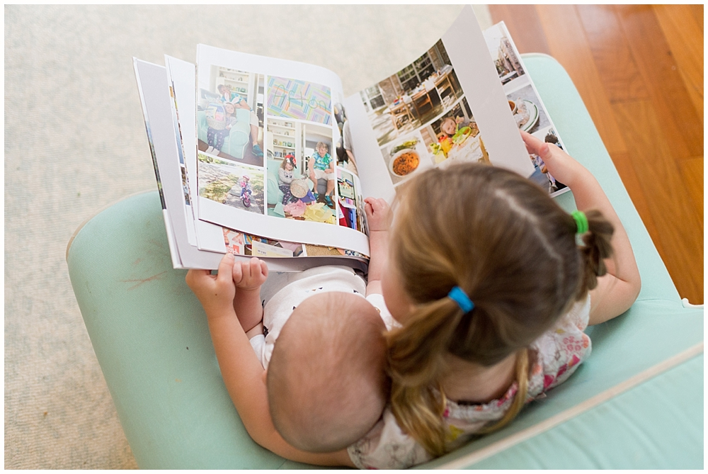 big sisters showing family photo book to baby brother - Blurb family photo albums