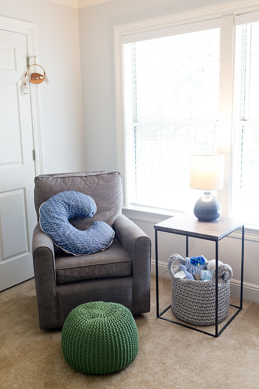 nursing glider, bobby pillow, and green pouf in baby boy's nursery