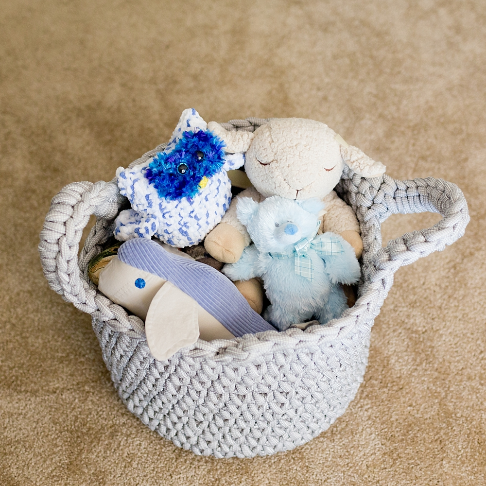 basket of baby boy's soft toys in nursery