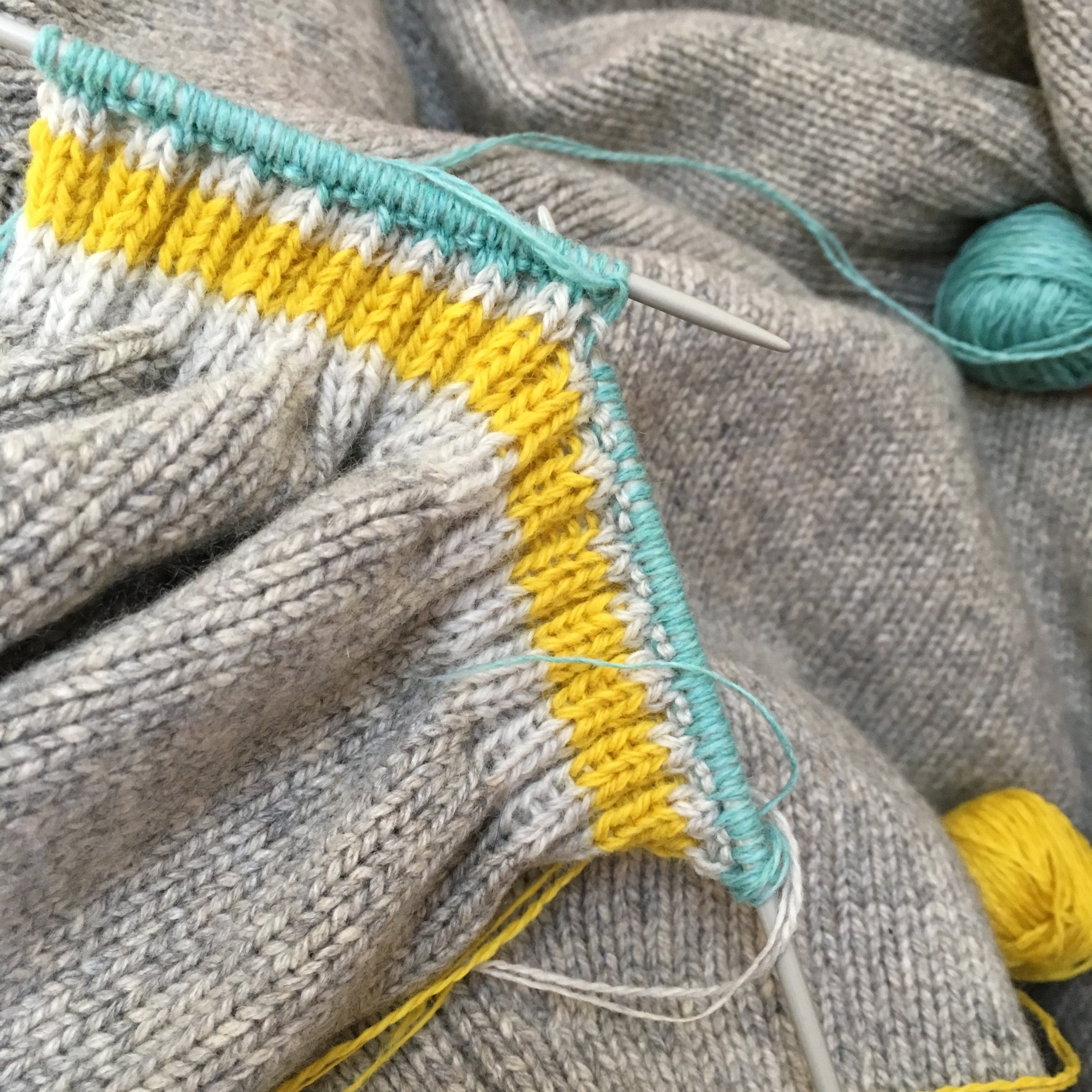 Re-knitting cuffs by hand, with bright stripes.