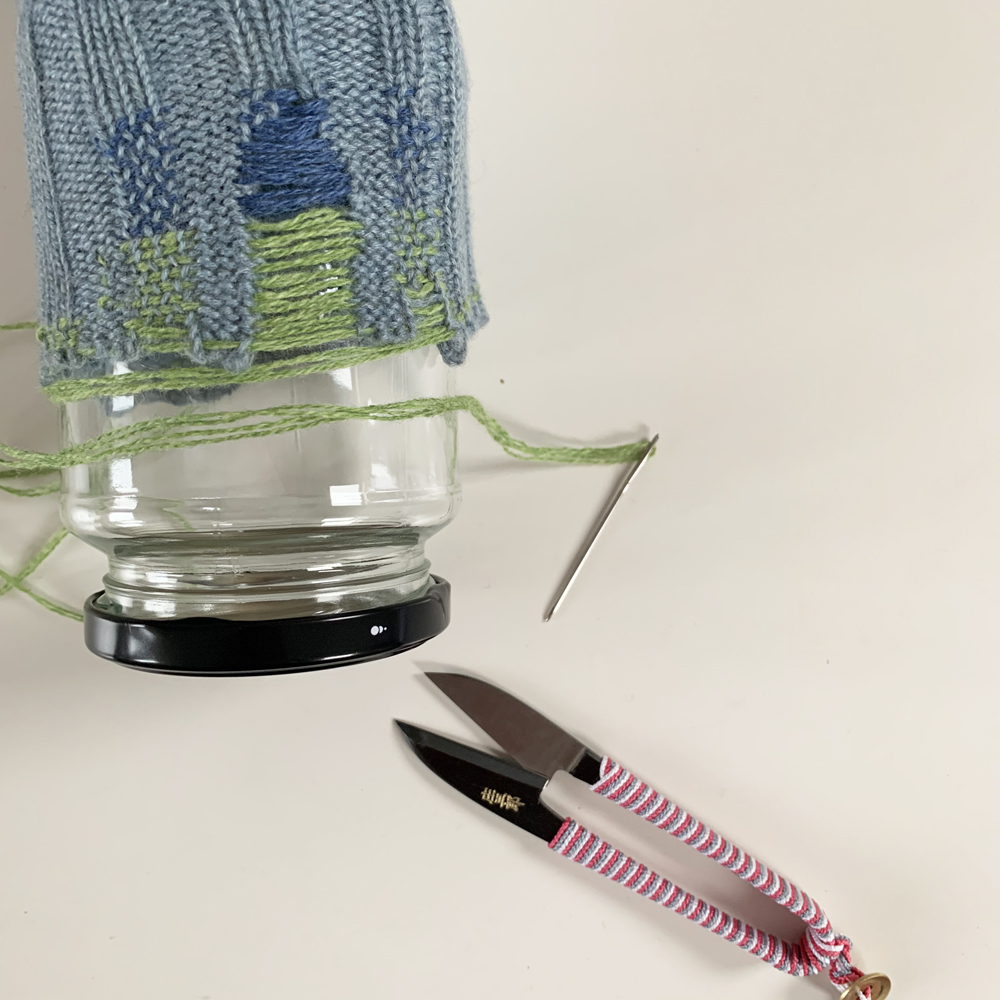Using a jam jar to work around to build up the extra fabric of the cuff.