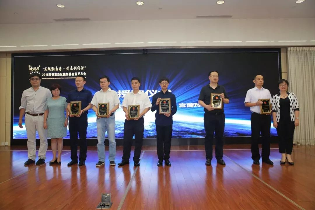 Zeliang Cao, Director of Administration at Saphlux (4th from right), is holding the award on the podium.