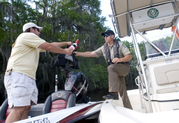 Game Warden Todd Long inspects boating equipment Thursday belonging to Owen Windham of Benton, La., while patrolling on Caddo Lake..jpg