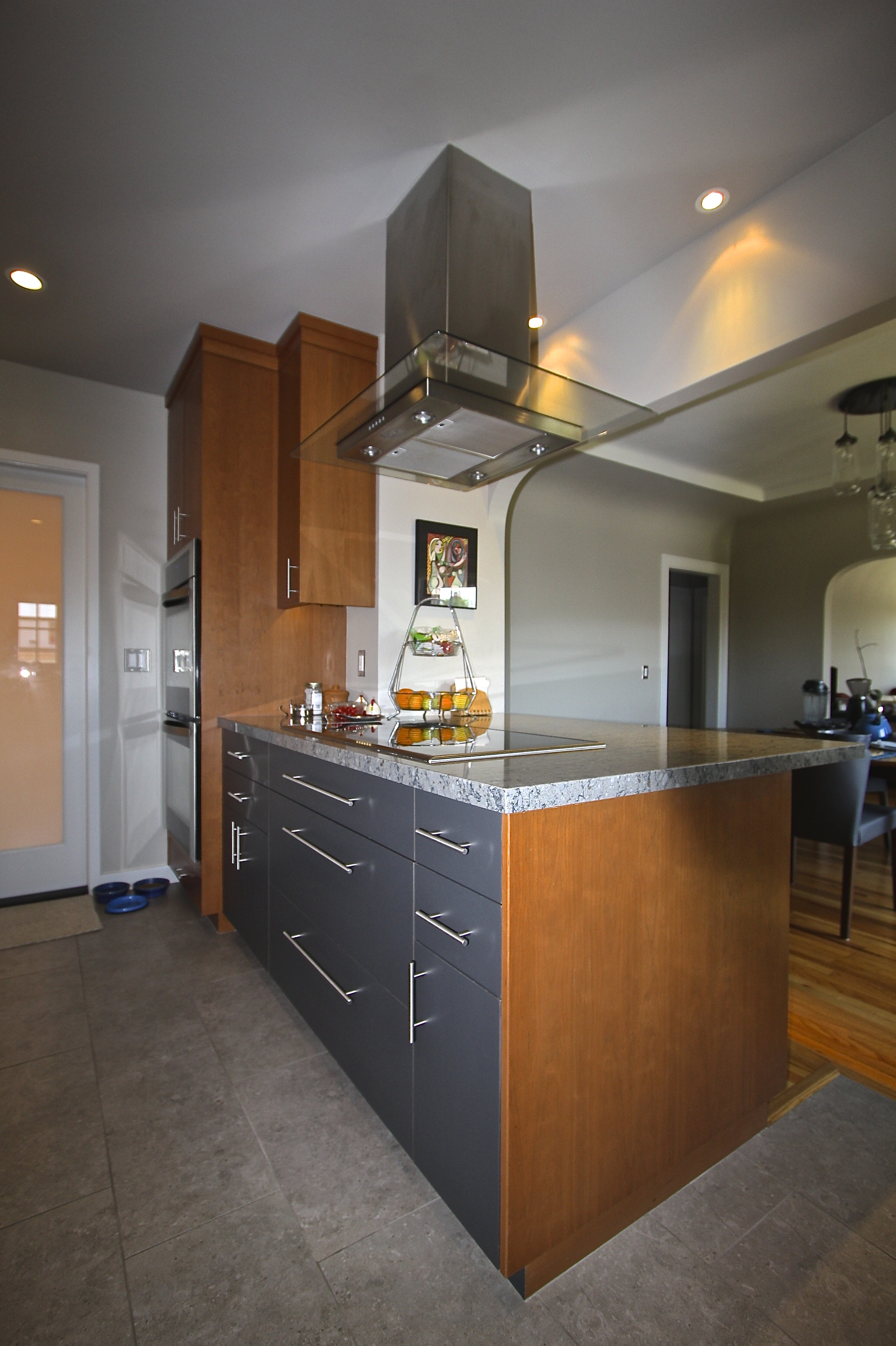 A nice mix of wood veneer and laminate cabinets create interest and balance the warm wood colors with cooler grays and blues of the tile, walls and countertop.