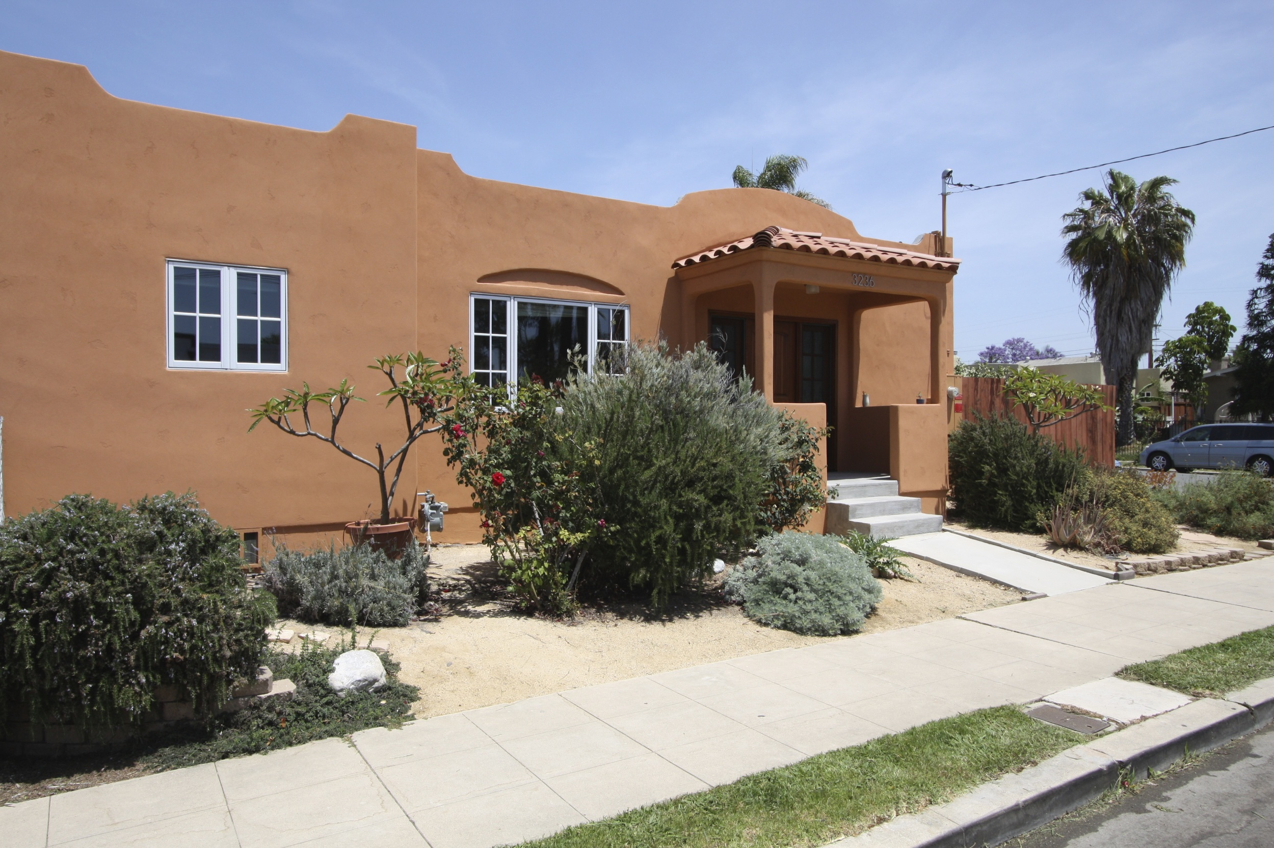After: New stucco in a terra cotta color and new clay tiles on porch roof really compliment the style of the house.