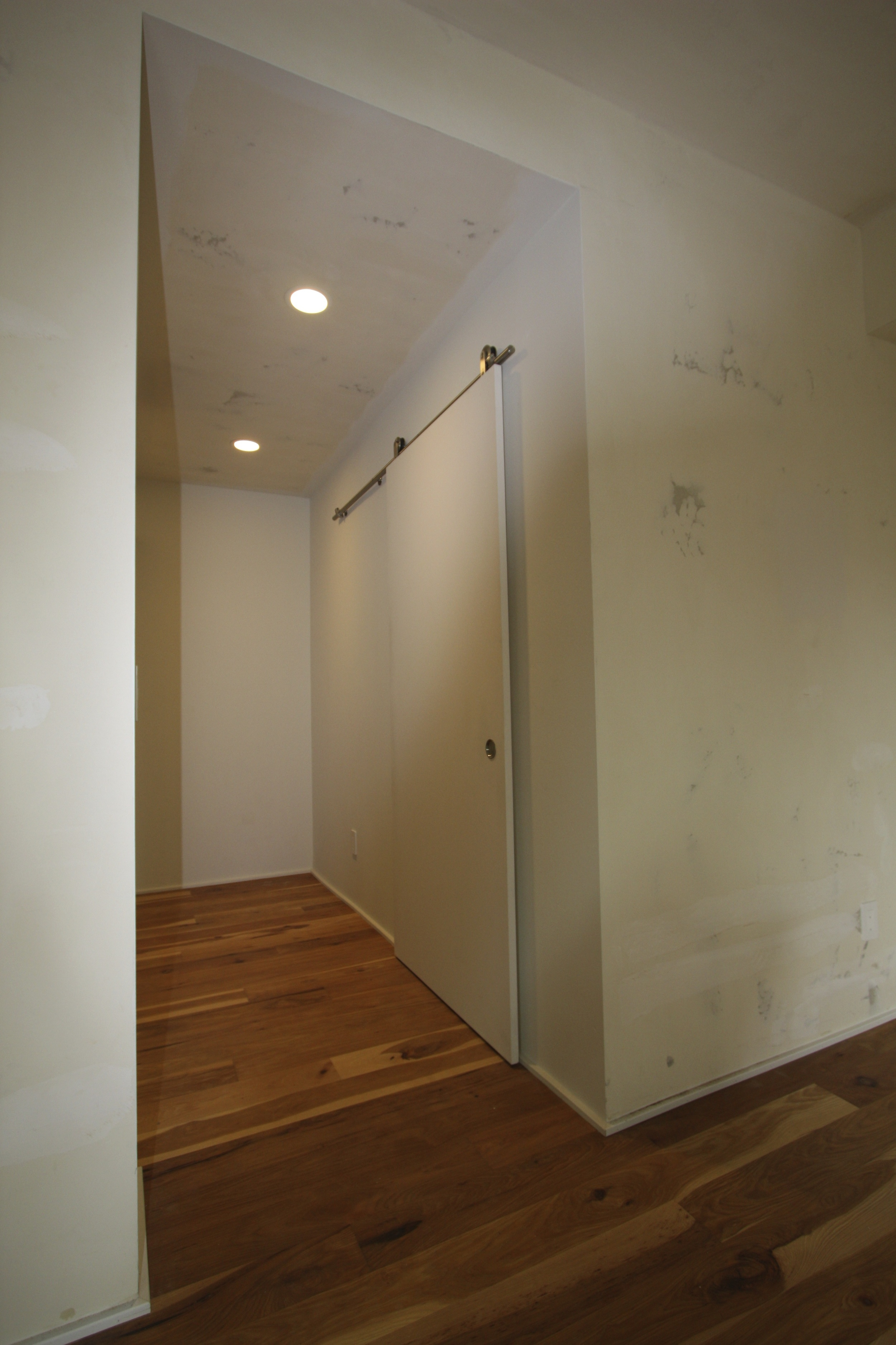 Hall accesses closet, laundry and bath. Sliding 'barn door' is seen here.
