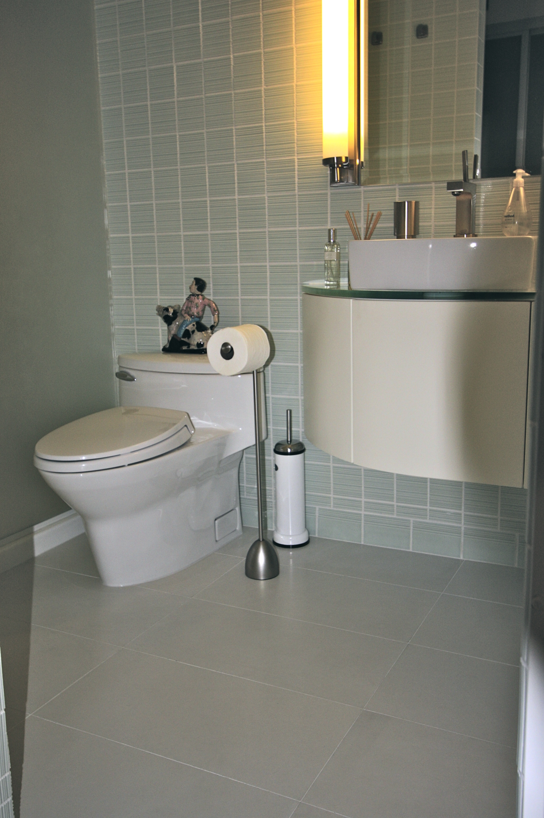 Bathroom includes custom made cabinet, glass top, floor to ceiling tiles.