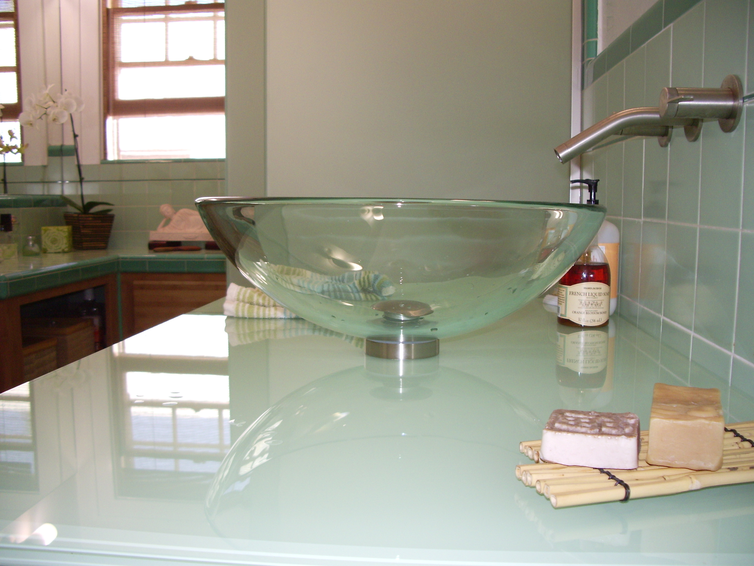 After:Glass vessel sink, glass countertop which was back-painted to match tiles and mattelux glass frameless tub / shower enclosure.