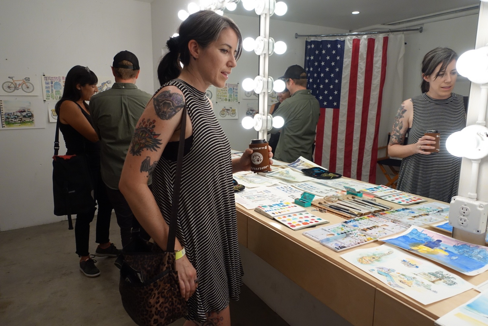 "Megan Rose perusing Chris McNally's art on display at the premiere of ""Roll With It"" photo by Jen Abercrombie"