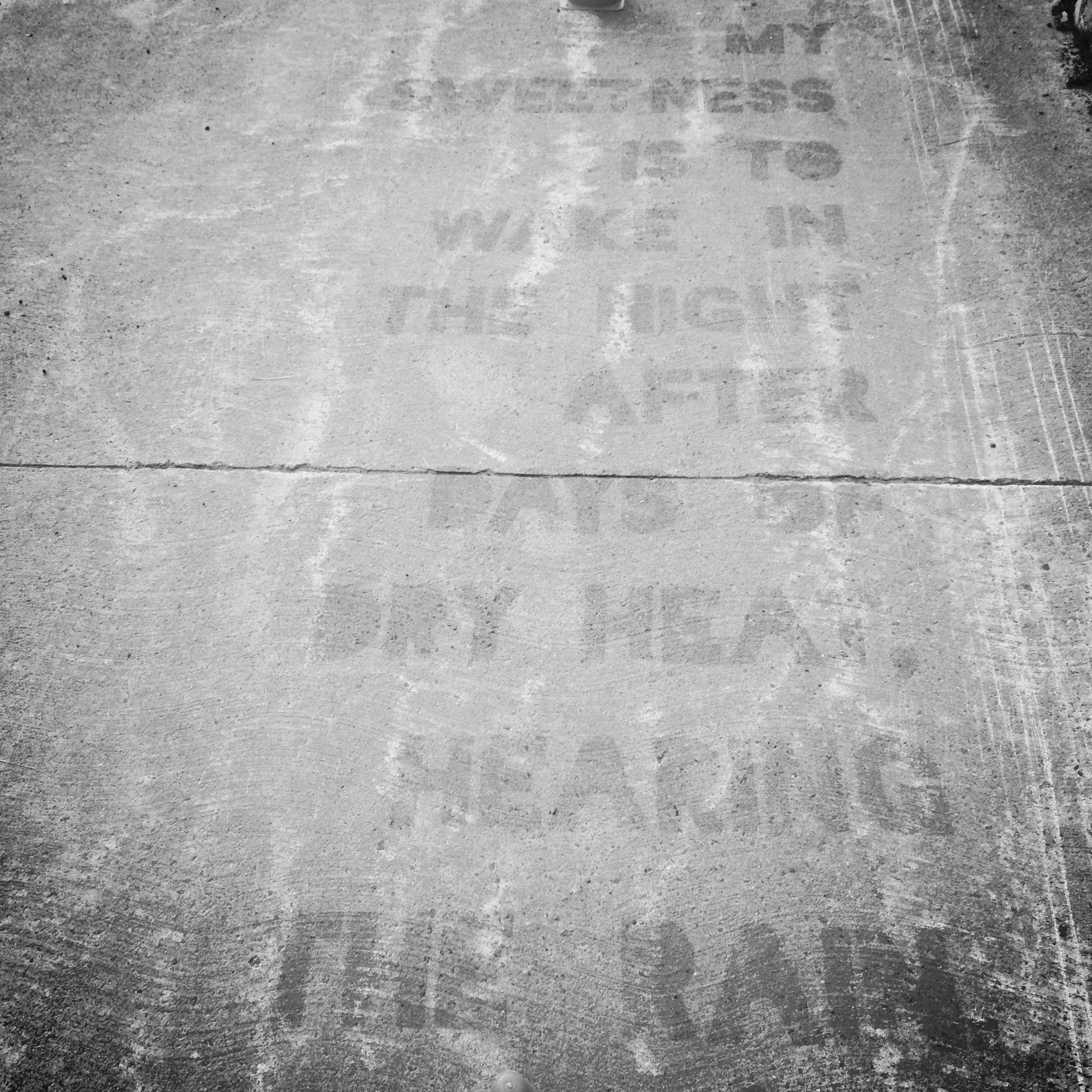 The spray is setting after stencilling. On a rainy day, it will appear the reverse (dry letters, wet ground).