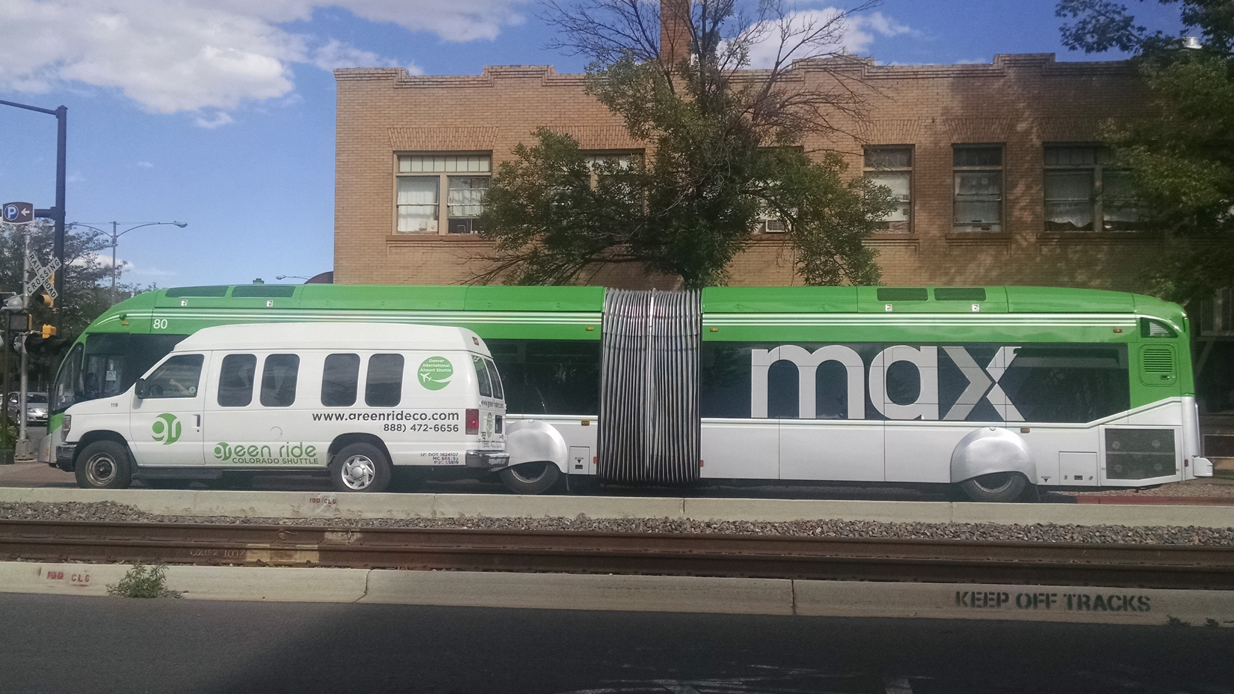 MAX bus with shuttle to the Denver airport in the foreground. Local and regional transportation.