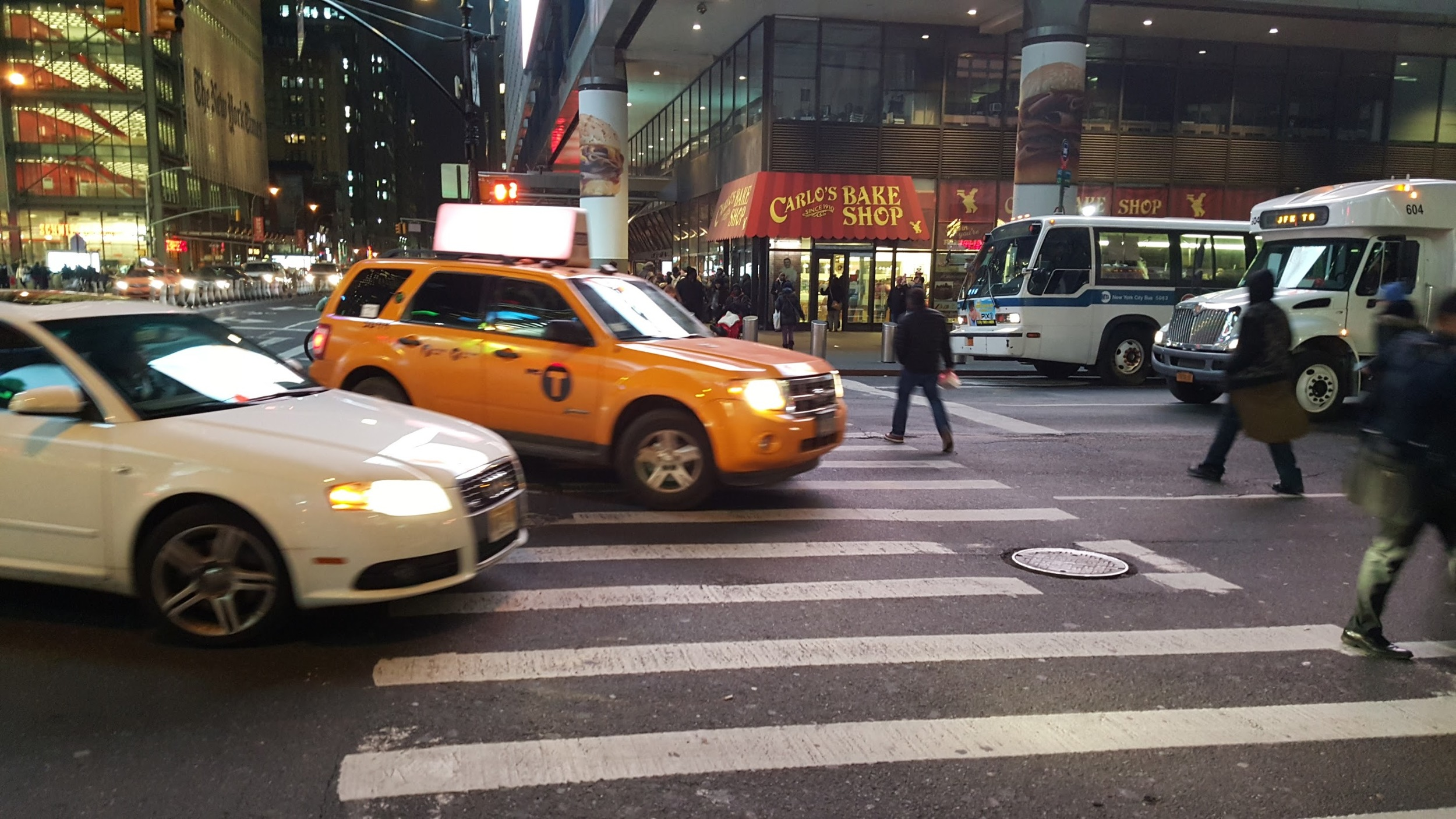 Cars turning into the crosswalk while people are crossing the street in Manhattan.