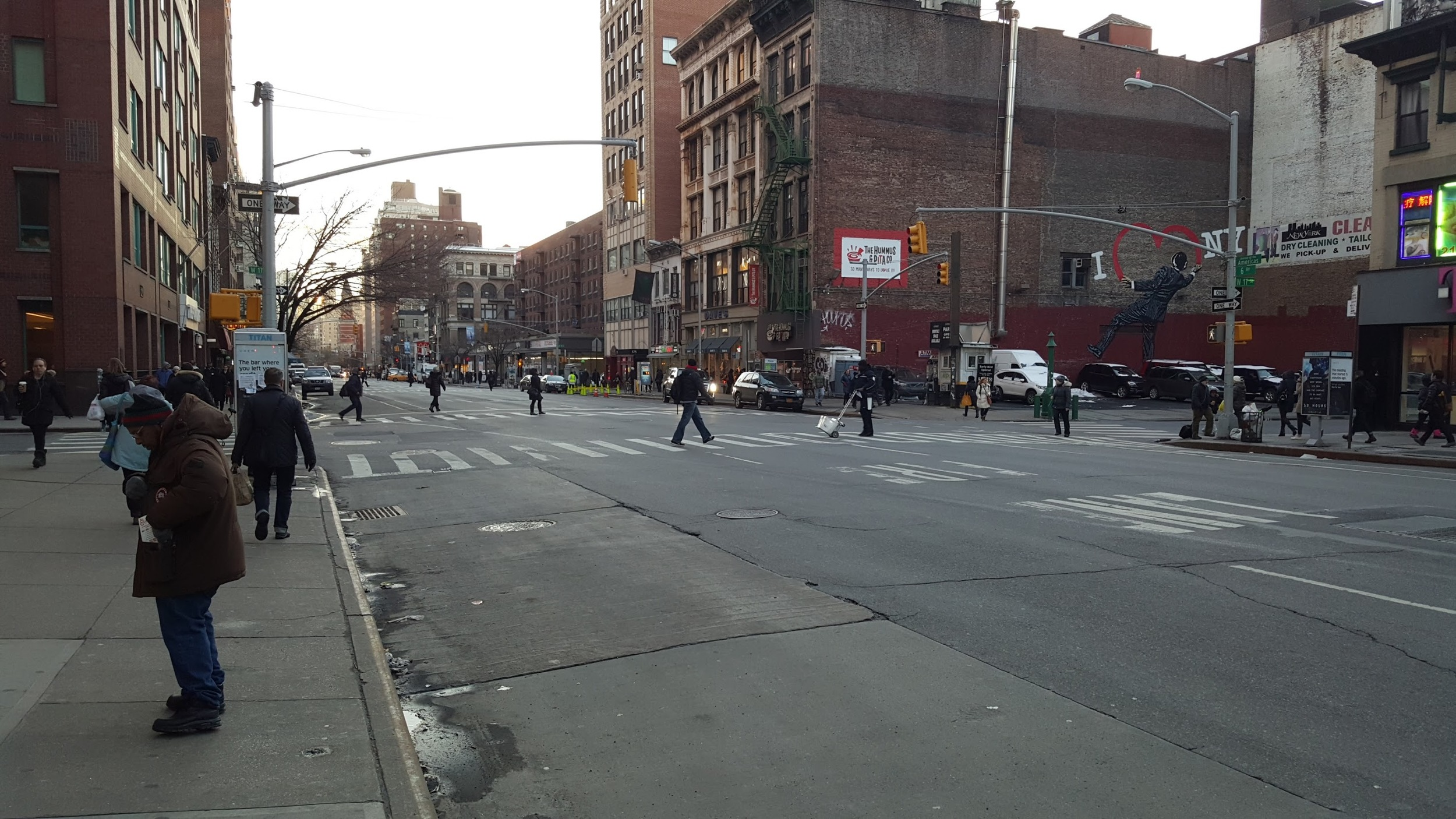 Everyone looking down the street in Manhattan as they cross. Perhaps they are not fully trusting the signal saying that nothing is going to hit them?