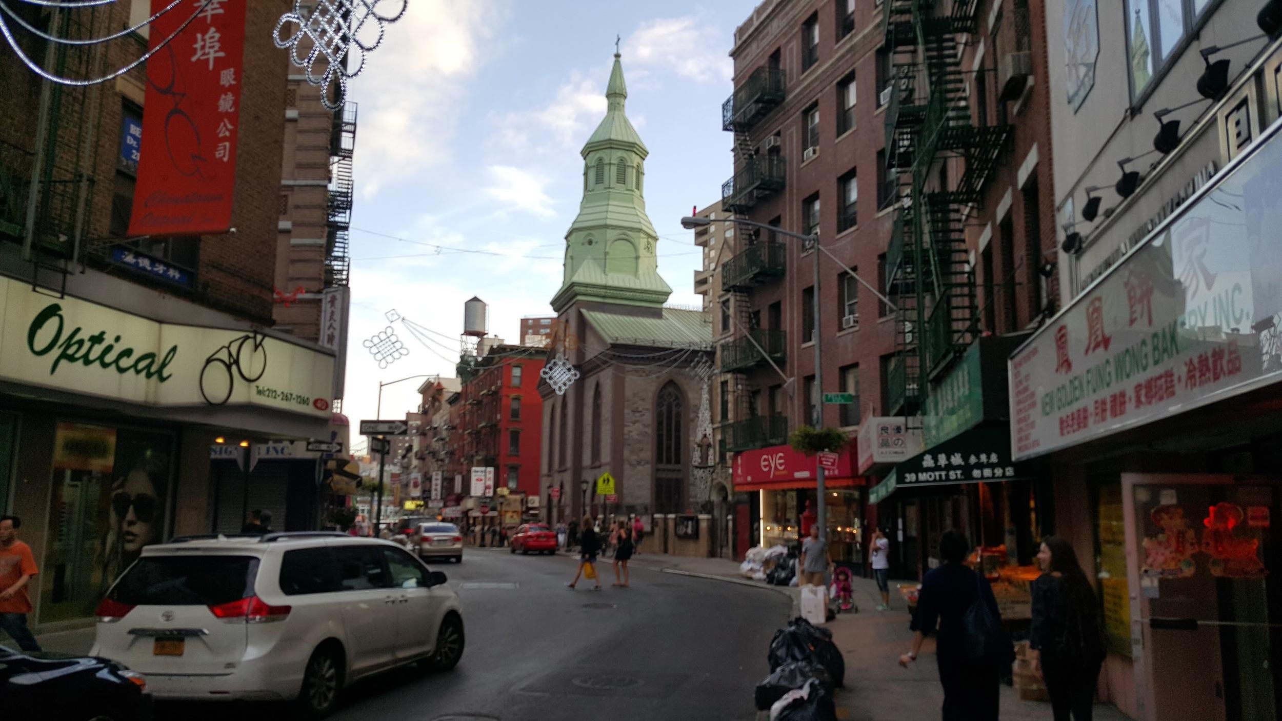 People jaywalking a street in Chinatown in Manhattan.