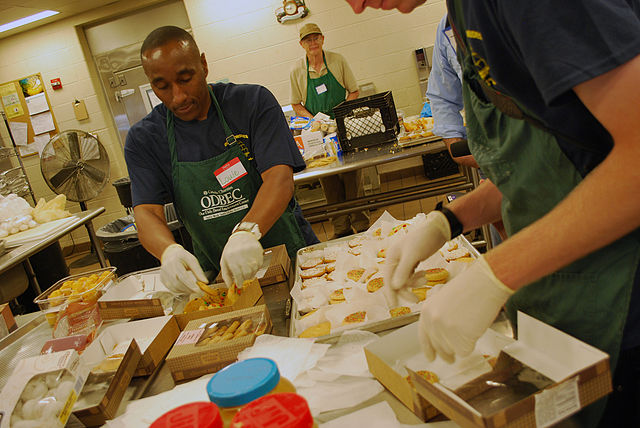 Volunteers prepare a meal for the hungry in a large-scale kitchen, something most houses of worship have ( source )