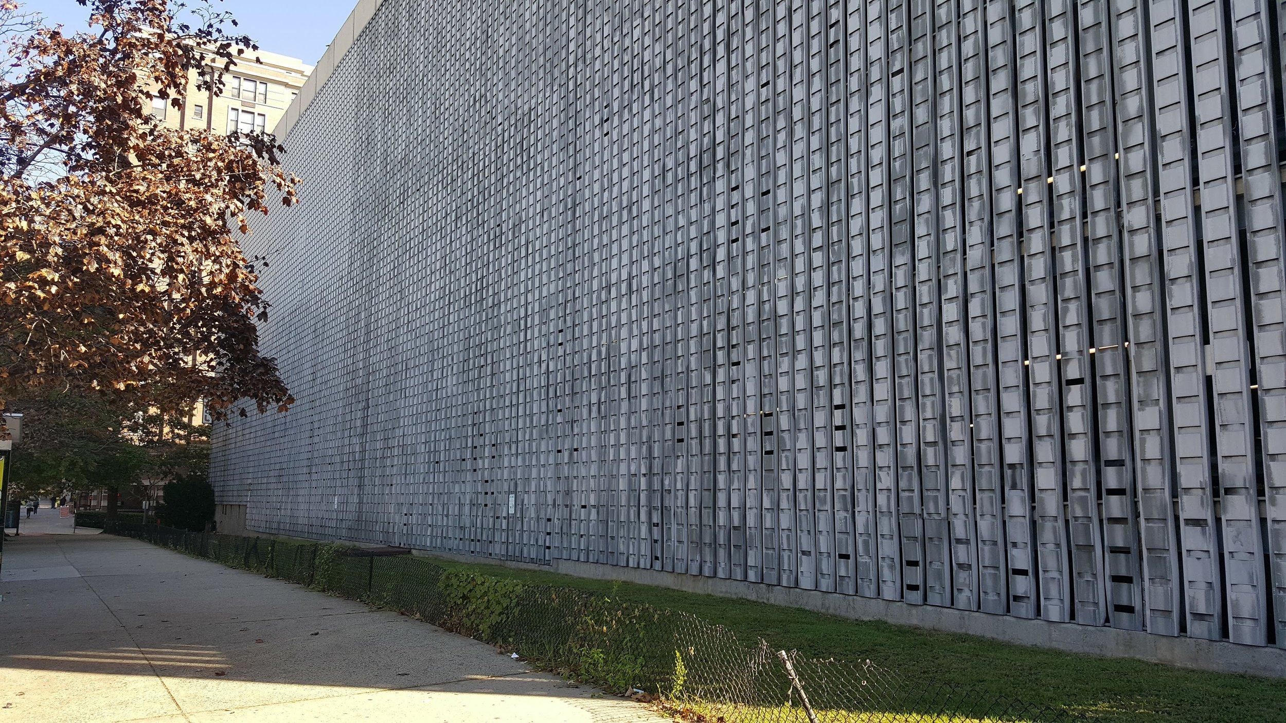 A bad parking garage in Hoboken, NJ that is one long blank wall.