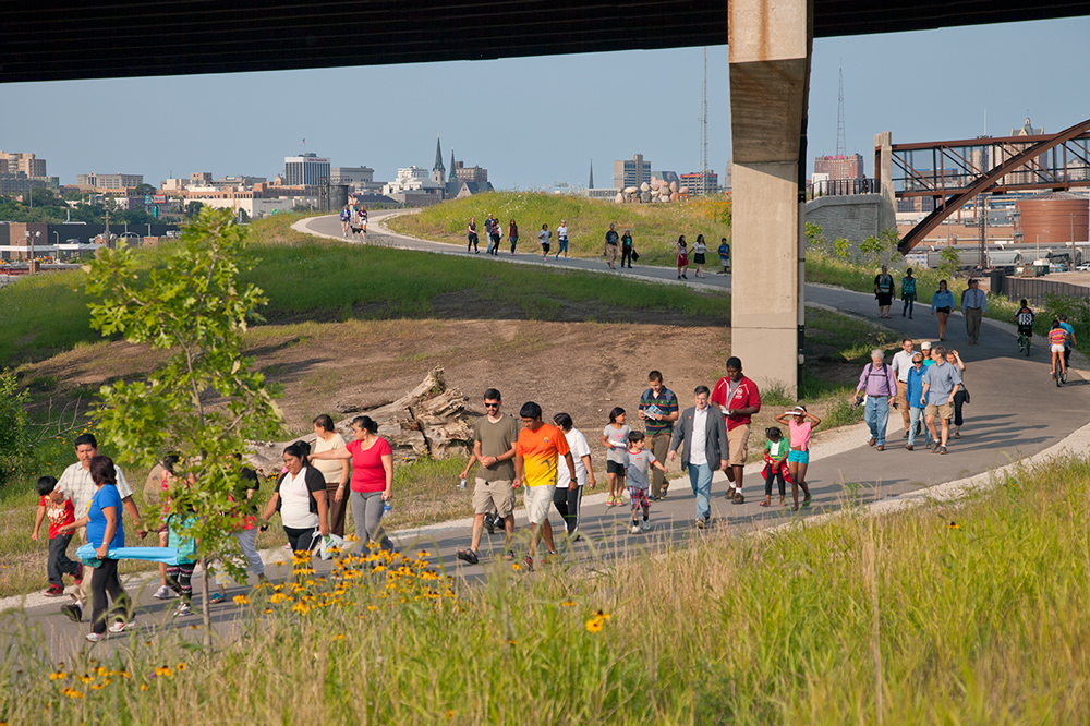 Milwaukee residents walk along the cross-town Hank Aaron Trail in Three Bridges Park, a new park created through grassroots efforts in the Menomonee Valley on a former brownfield. The event was one of several community walks led by Mayor Tom Barrett.