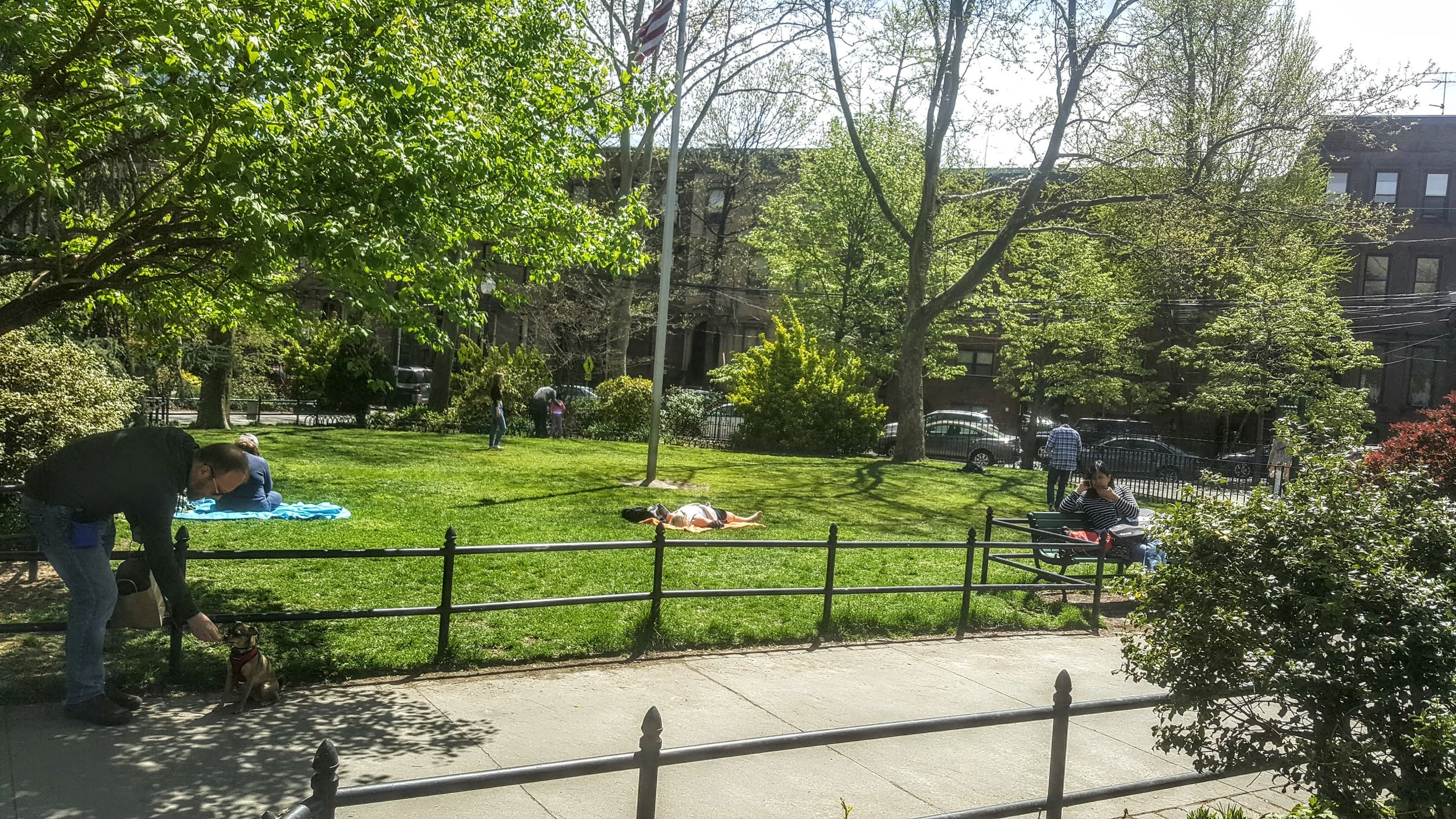 People enjoying the lawned area of Van Vorst Park.