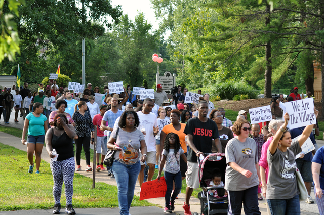 Protesters march in the street in Ferguson following the shooting of Michael Brown ( Source )