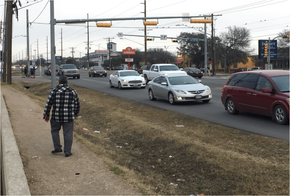 A lack of safe — or any — walking facilities on North Lamar Blvd forces people to walk in the ditch. (Source: Heyden Walker)