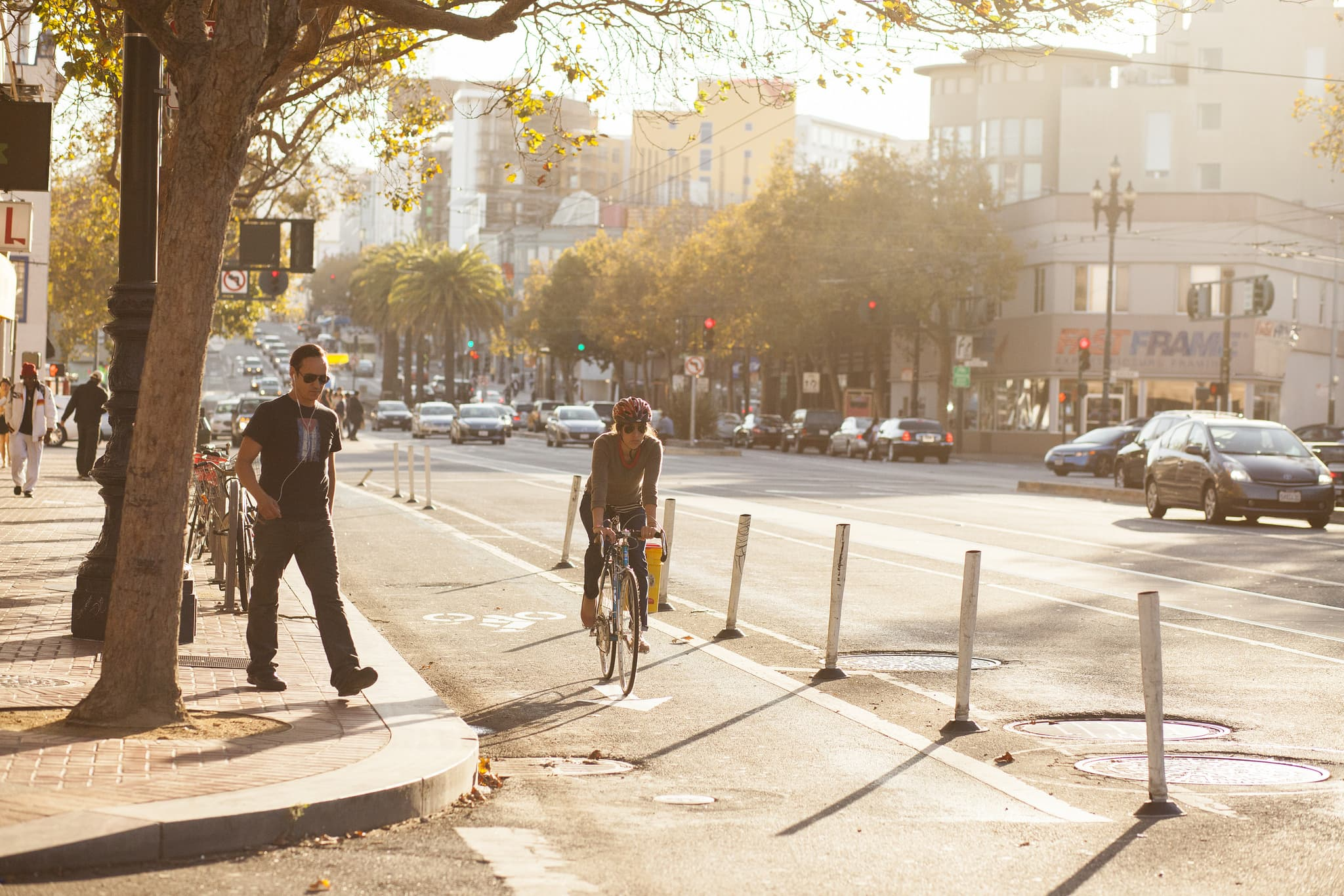Protected bike lanes create an environment where pedestrians feel safer walking and cars still have easy access to shops along the street. (Source: Green Lane Project)