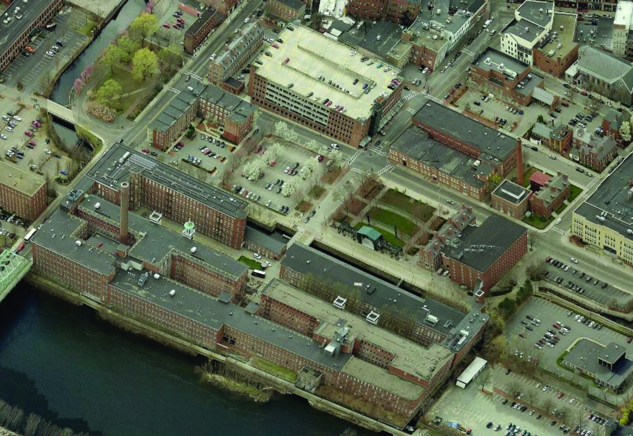Lowell, MA, dedicated empty spaces in its municipal parking structures (top of image) to serve new apartments in rehabilitated buildings (bottom of image).   (Photo credit: Bing Maps)