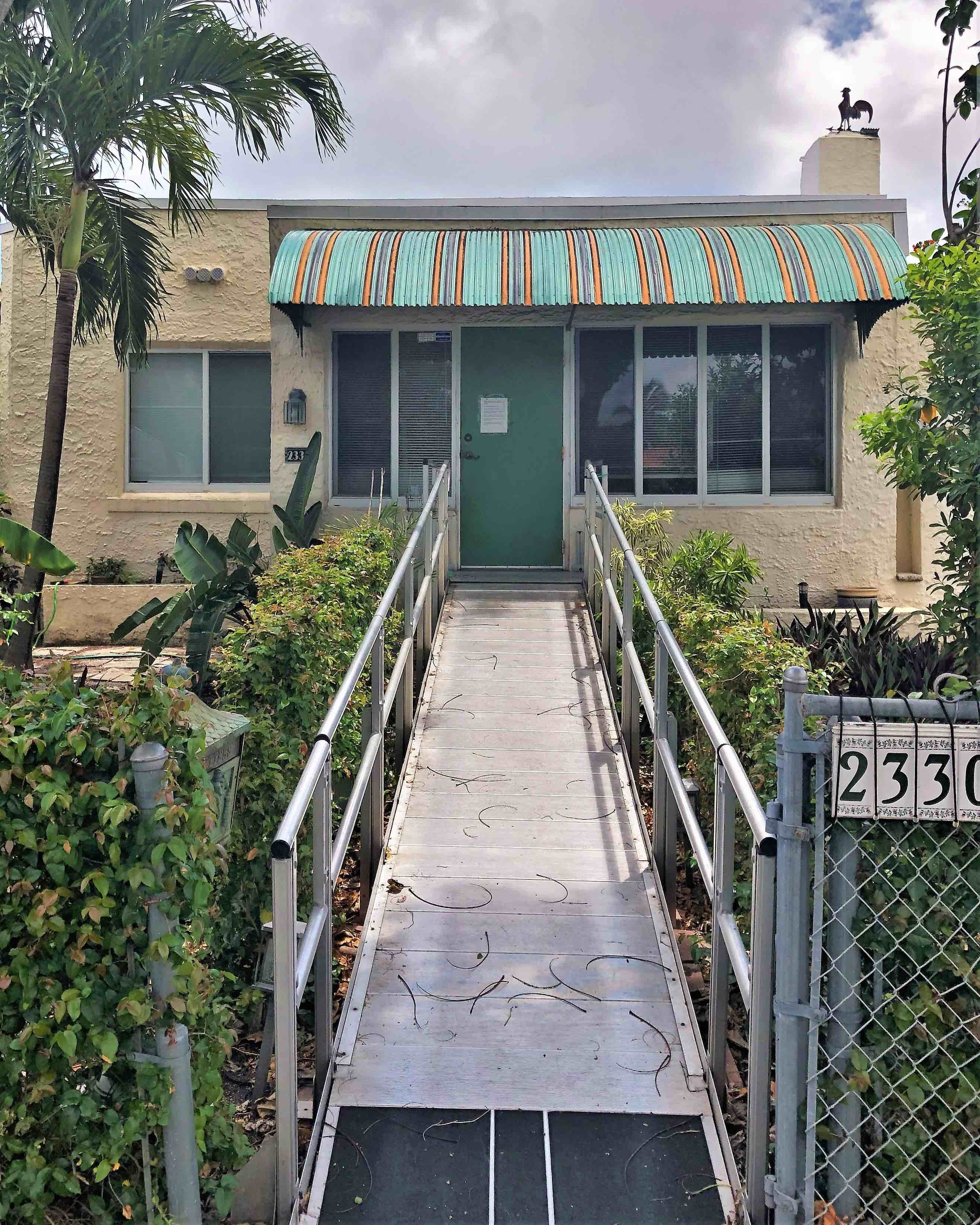 A ramp with non skid tape runs front door to sidewalk and serves a house elevated far above the flood plain in Miami, ground zero for sea-level rise.
