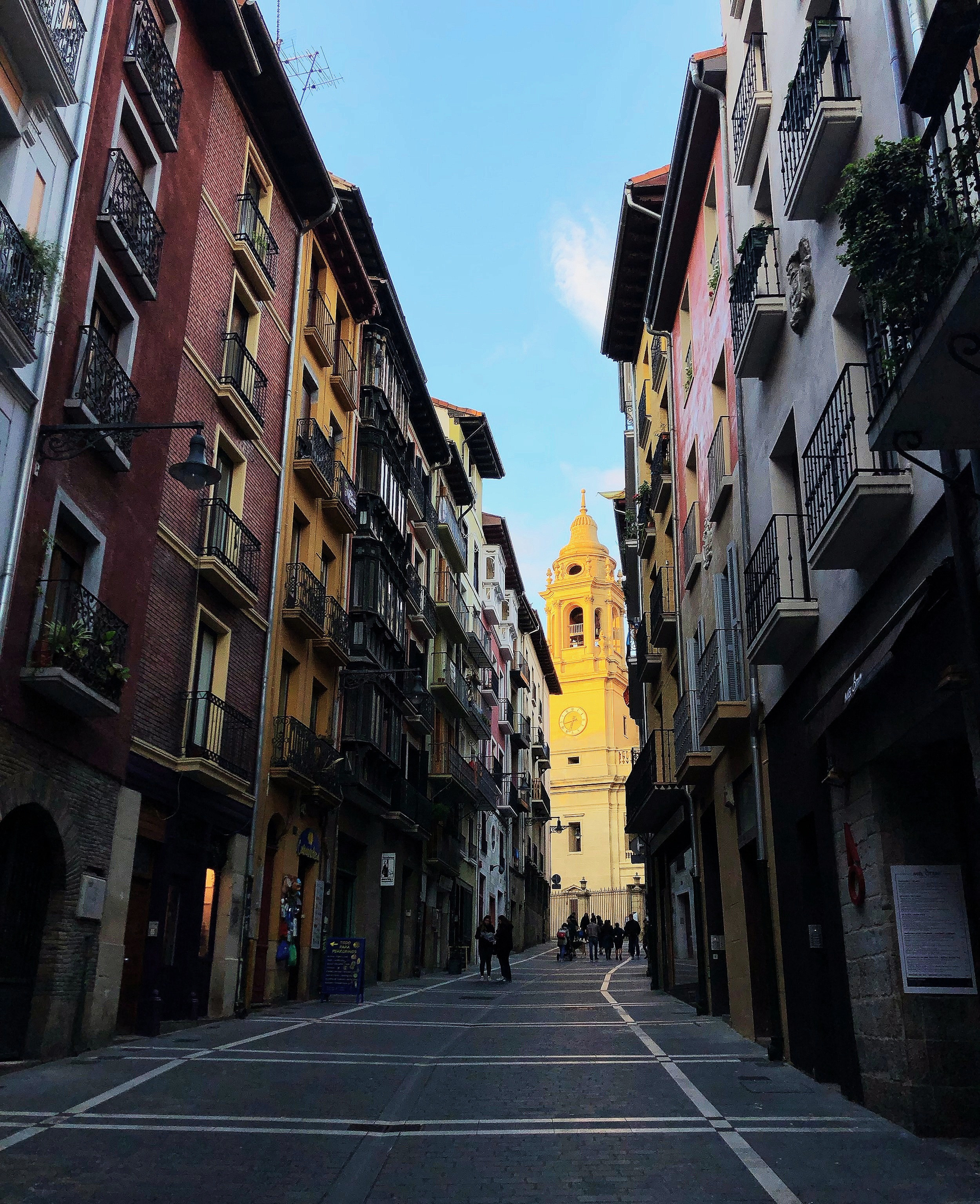 A normal street in the old town of Pamplona. Cars are able to be driven here but rarely are. The Pamplona Cathedral glows in a setting sun at the end of the street.