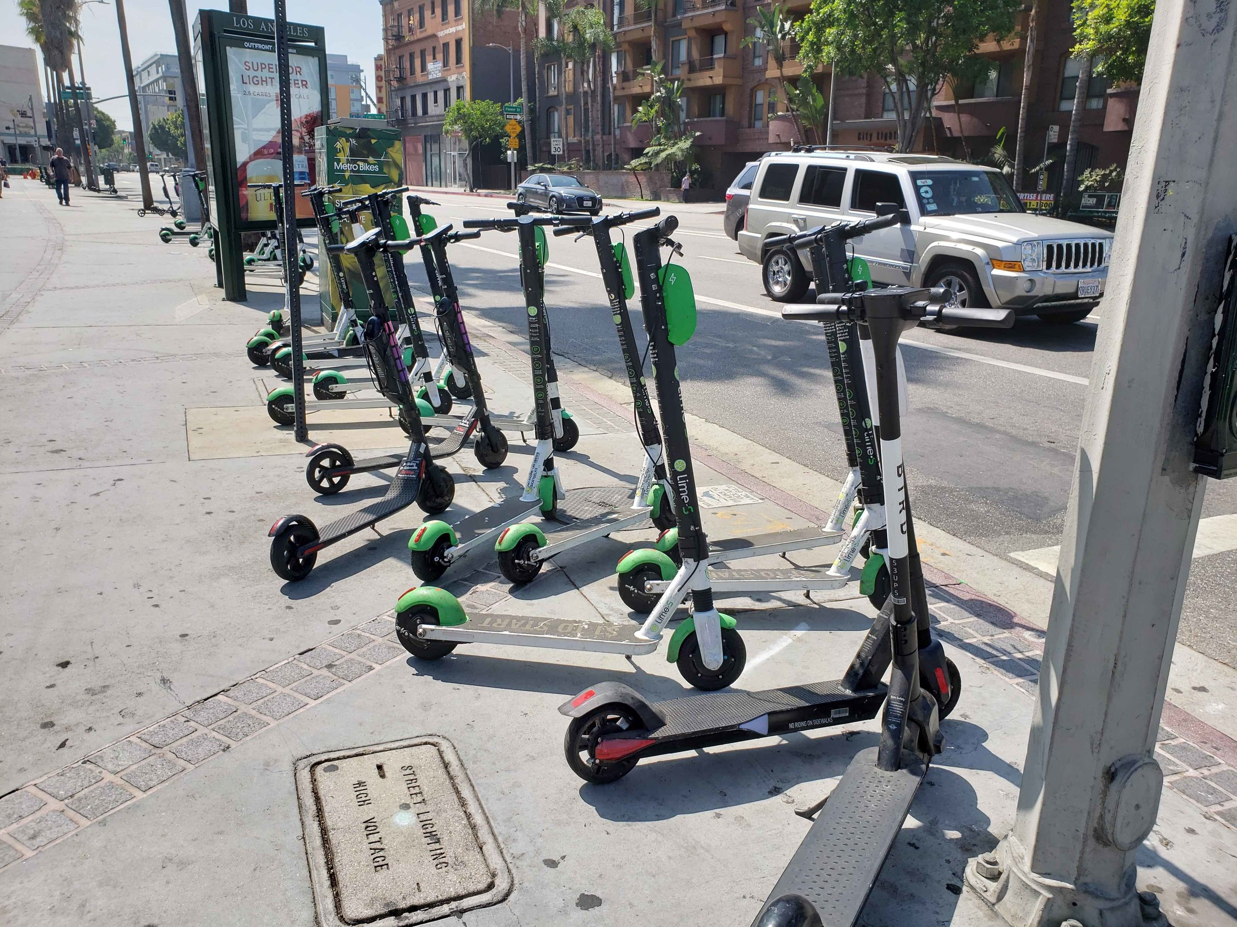 Scooters lined up in downtown Los Angeles—social norms about parking them out of the way of sidewalk users seem to have emerged in the absence of any formal parking arrangements. (Photo by Daniel Herriges)