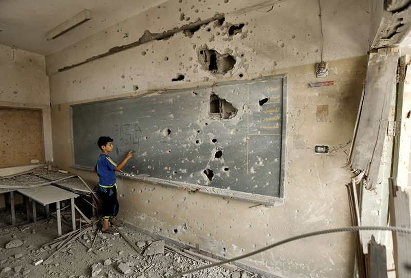 A Palestinian boy writes on a shrapnel riddled backboard at the heavily damaged Sobhi Abu Karsh school in Gaza City's al-Shejaea neighborhood on August 5, 2014. (Mohammed Abed)