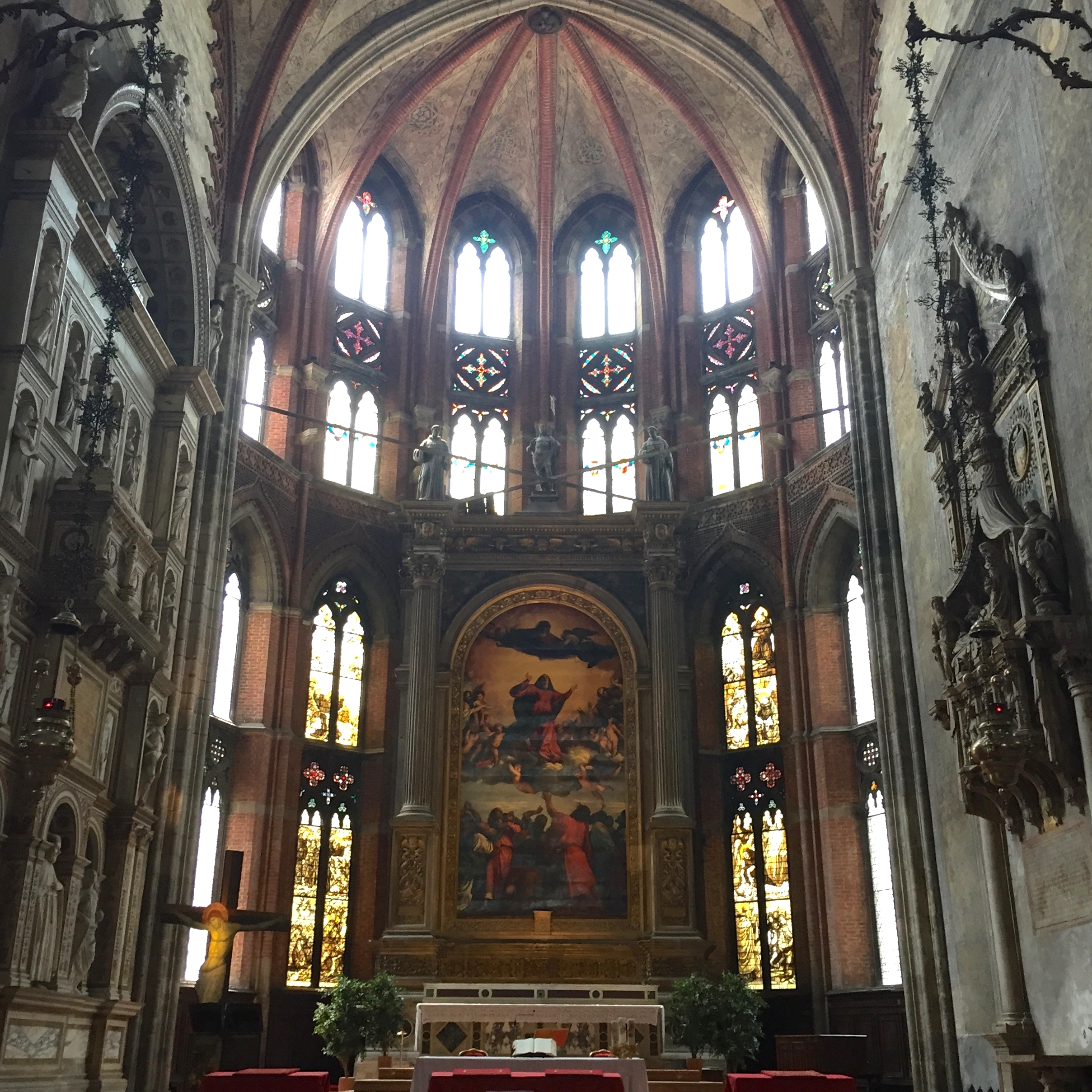 View of the stained glass windows and altarpiece in the Basilica dei Frari.